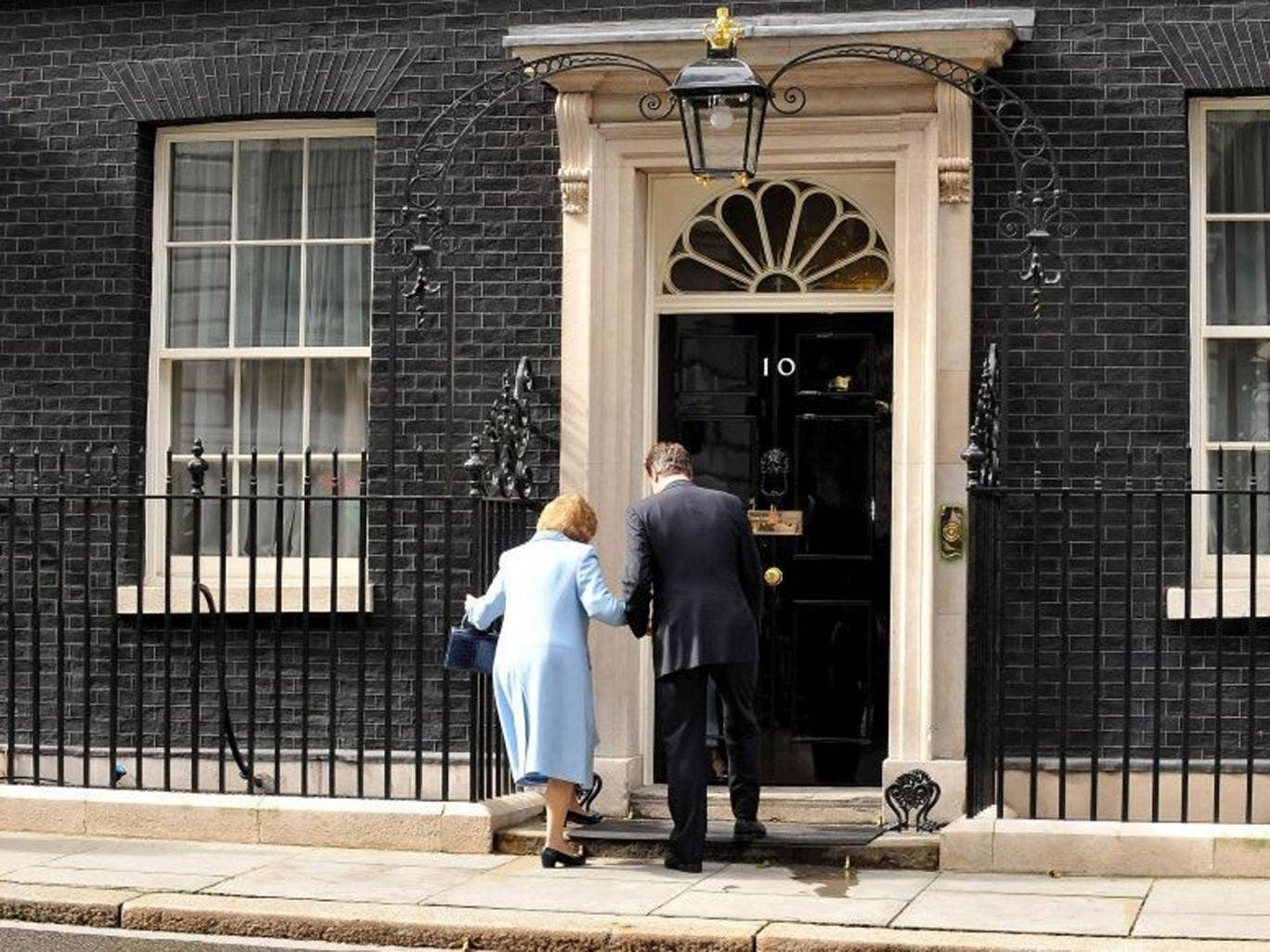 June 2010: Prime Minister David Cameron helps Baroness Thatcher into 10 Downing Street