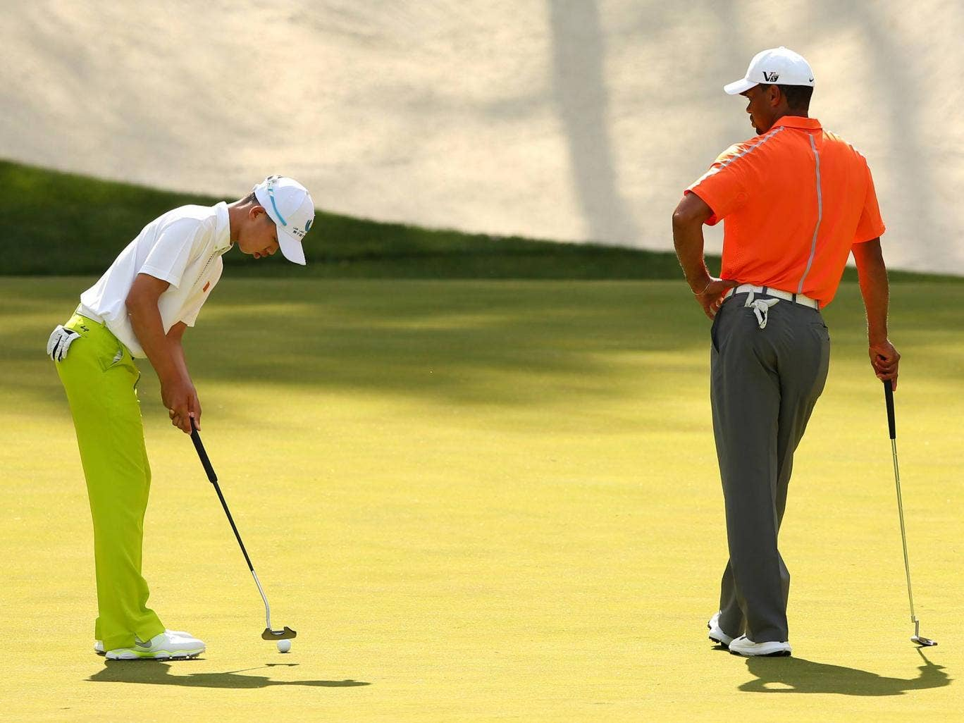 Tianland Guan practices alongside Tiger Woods at Augusta