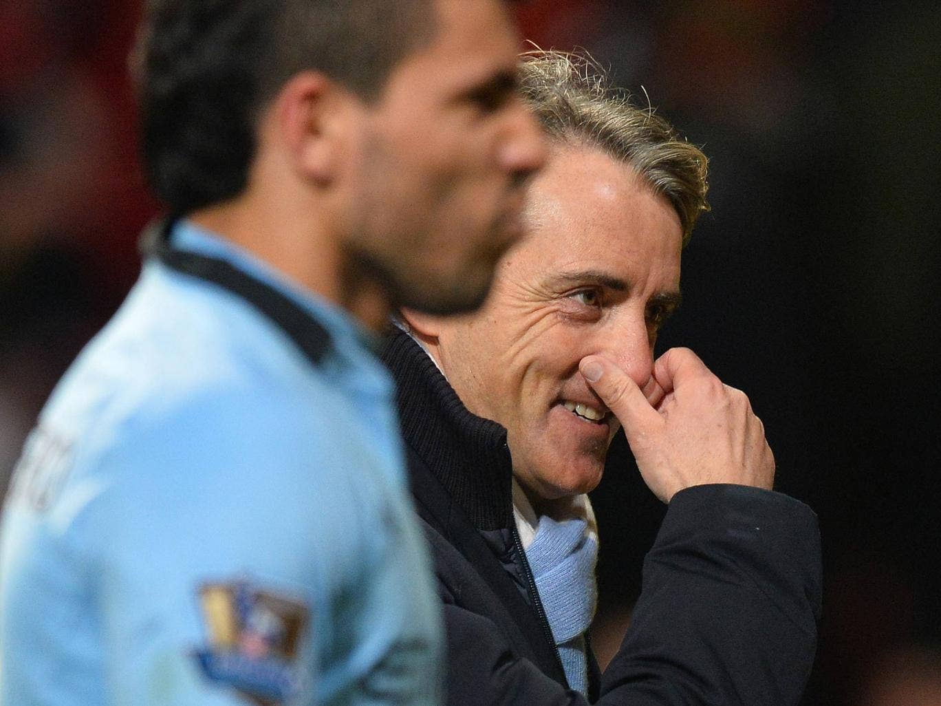 Roberto Mancini leaves Old Trafford with a smile on his face after victory over United