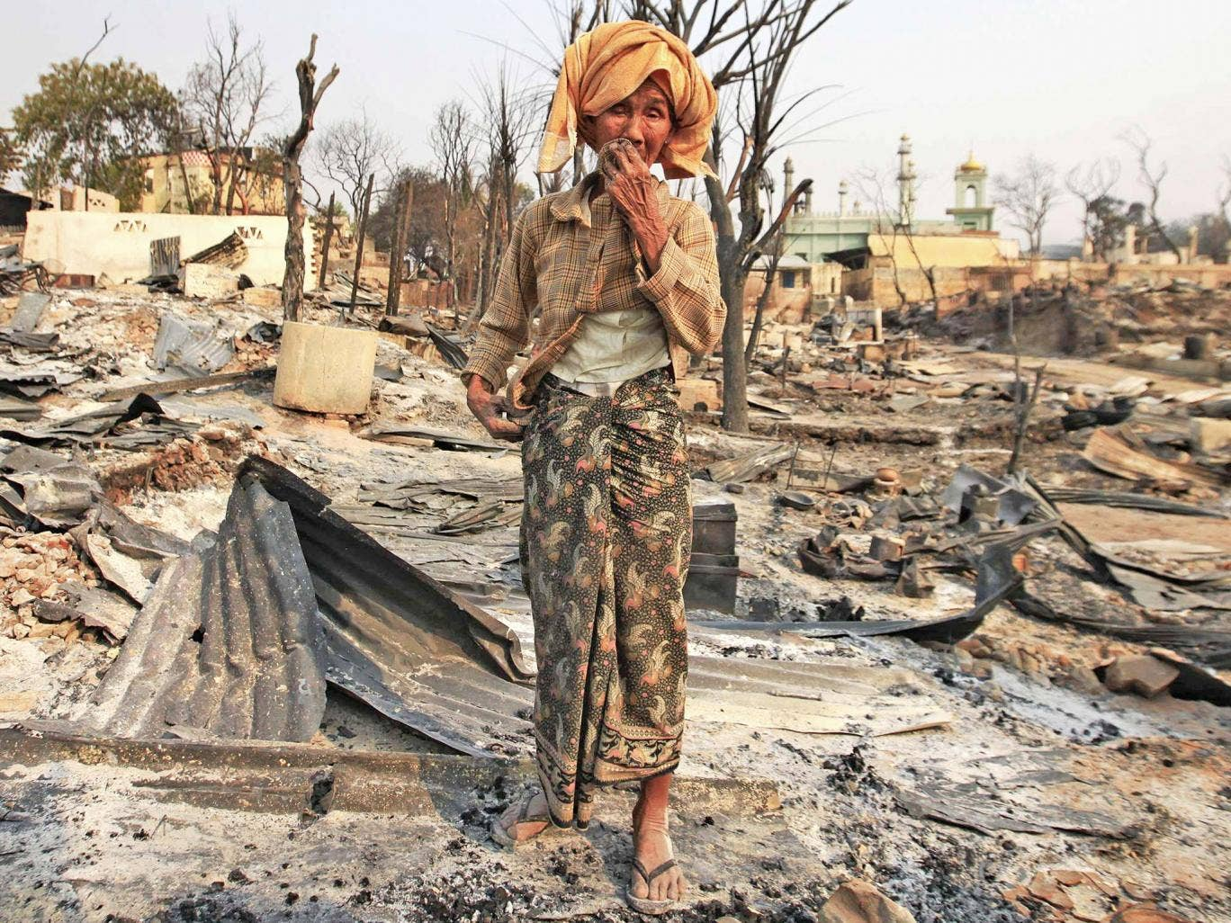 A woman cries for her home, burnt down during the riot in Meiktila in March