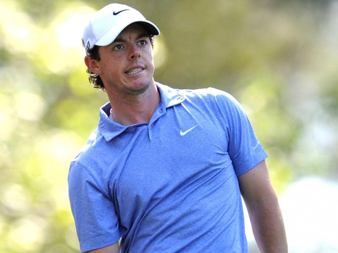 Rory McIlroy watches his ball on the course during practice