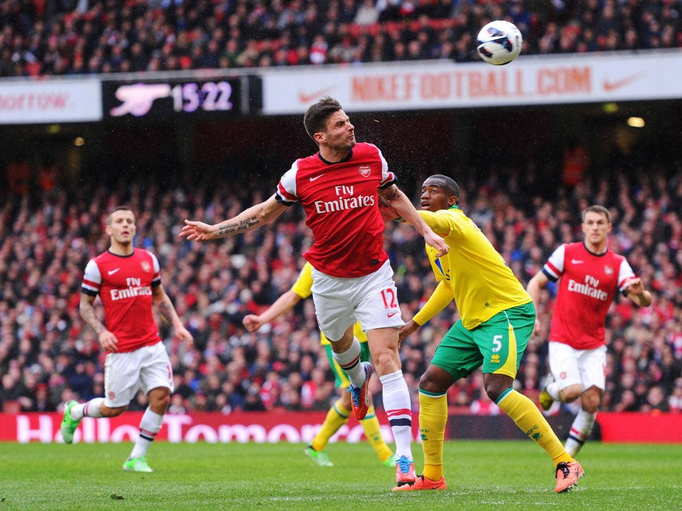 Olivier Giroud of Arsenal and Sebastien Bassong of Norwich City compete for the ball