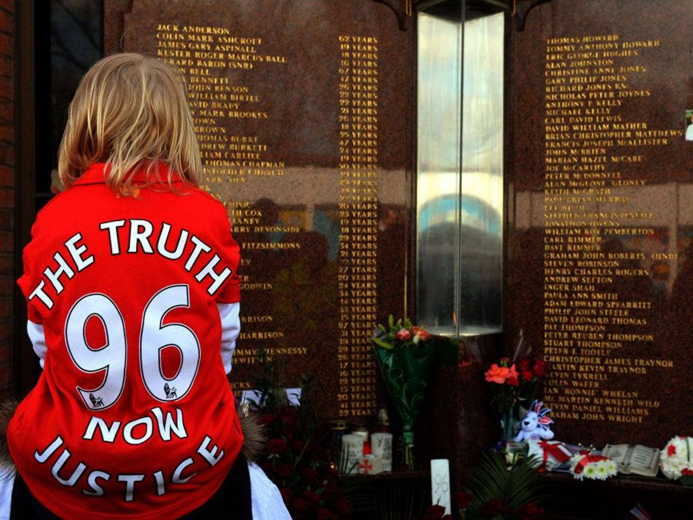 "A child wears a Jersey bearing the writing  ""Justice for the 96"" in front of the Hillsborough Memorial at Liverpool FC's Anfield football ground"