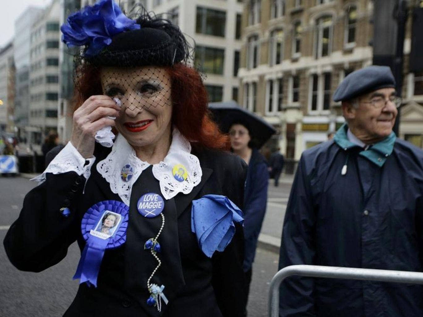 Gloria Martin, a supporter of former British prime minister Margaret Thatcher, wipes her tears as she joins others by the route of the funeral procession at St Paul's Cathedral