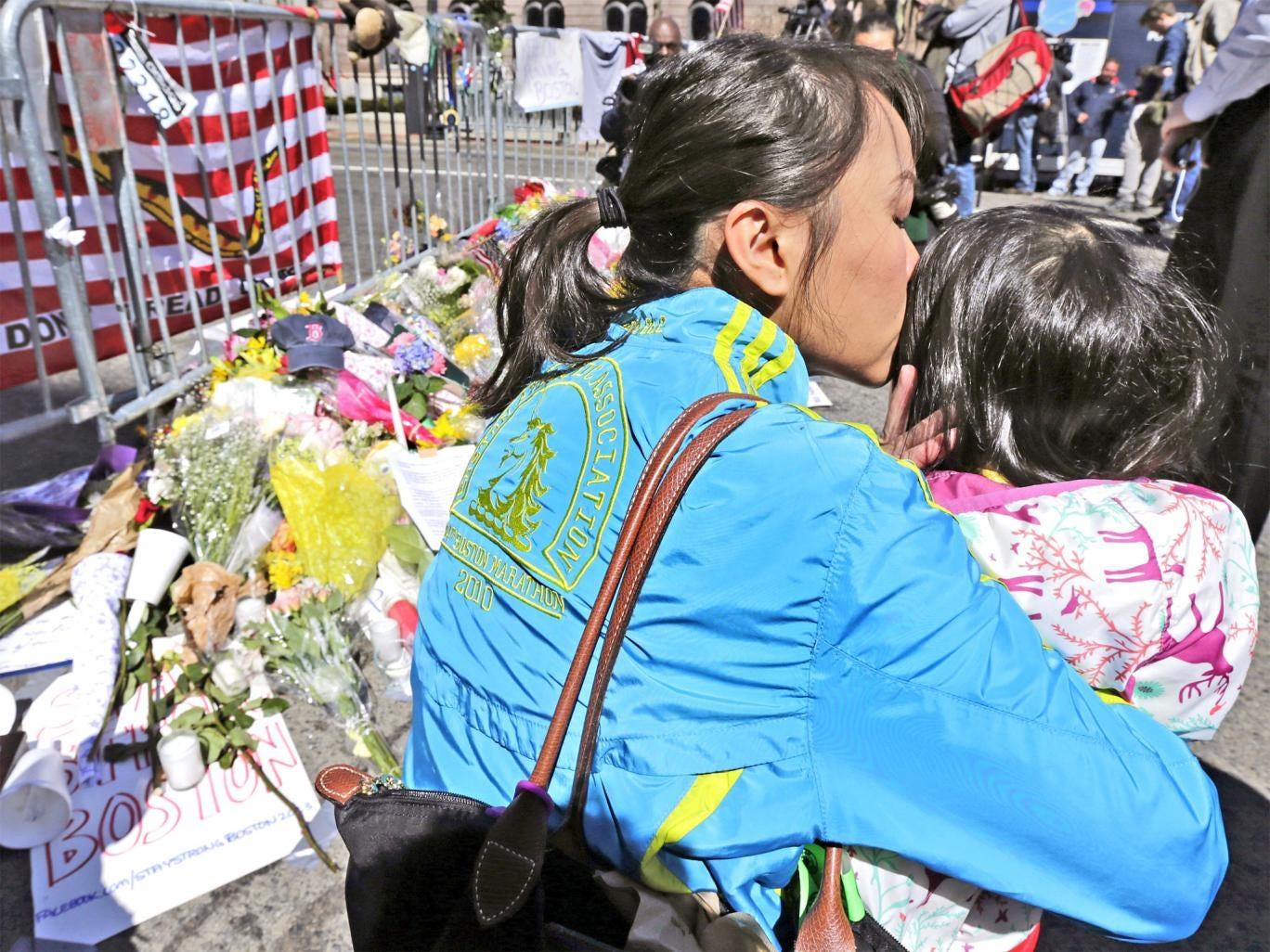 Marathon runner Vu Trang kisses her two-year-old daughter Cara at a memorial in Boylston Street