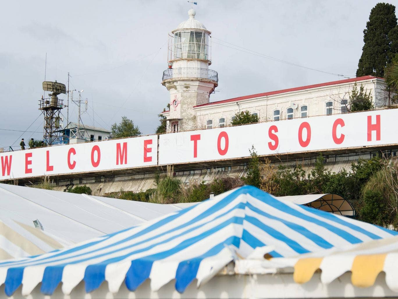 A large 'Welcome to Sochi!' sign hangs above the waterfront area in central Sochi