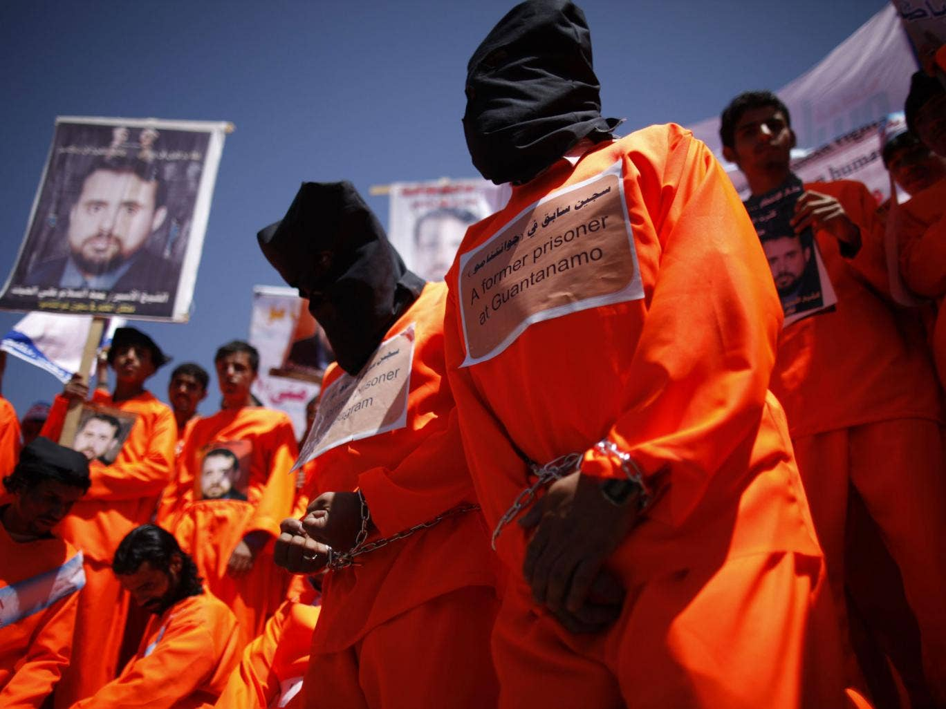 Former Guantanamo Bay detainees wear black hoods during a protest