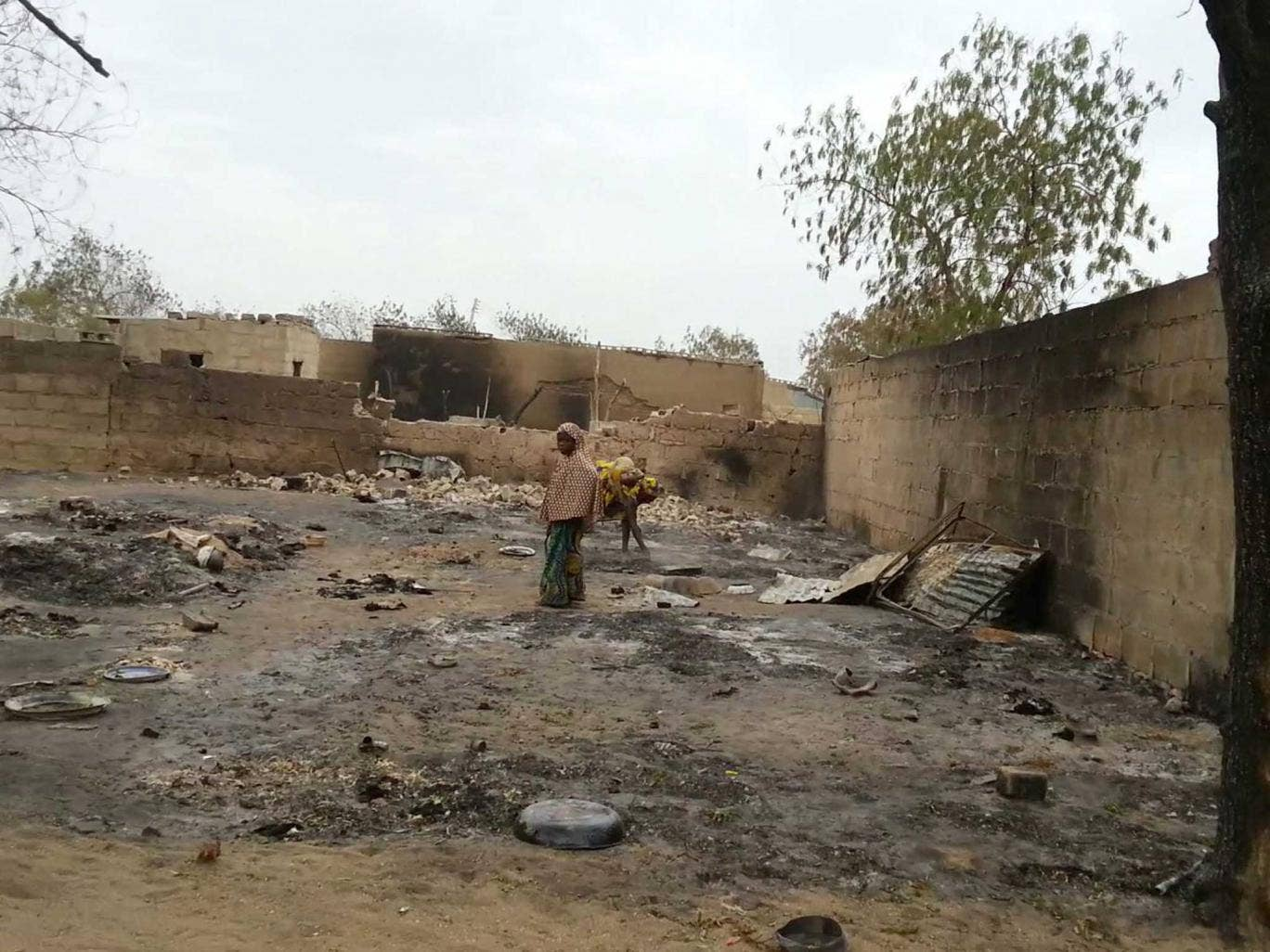 A young girl stands amid the burned ruins of Baga, Nigeria