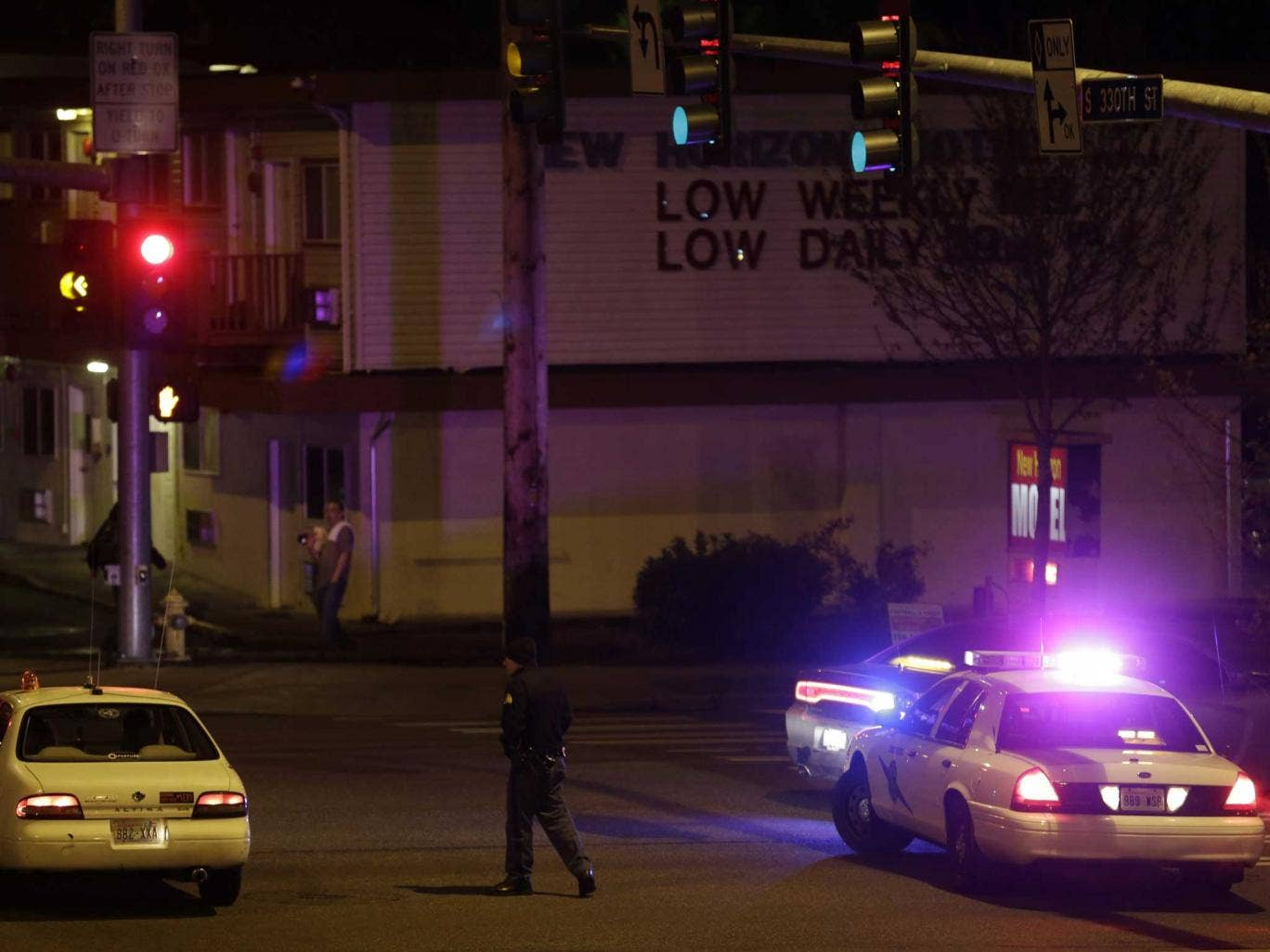A Washington State Patrol trooper directs a driver away from a street blocked off several blocks from the scene of the shooting that police said left five people dead