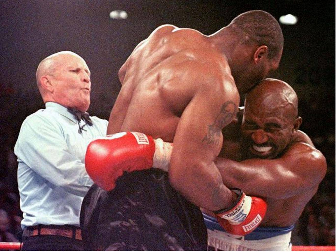The referee Mills Lane intervenes after Mike Tyson bit Evander Holyfield (right) during their infamous encounter in June 1997