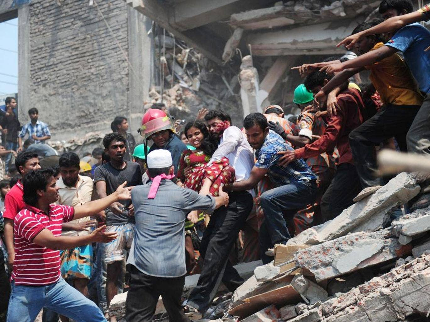 Bangladeshi volunteers evacuate an injured garment worker after an eight-storey building collapsed in Savar, on the outskirts of Dhaka