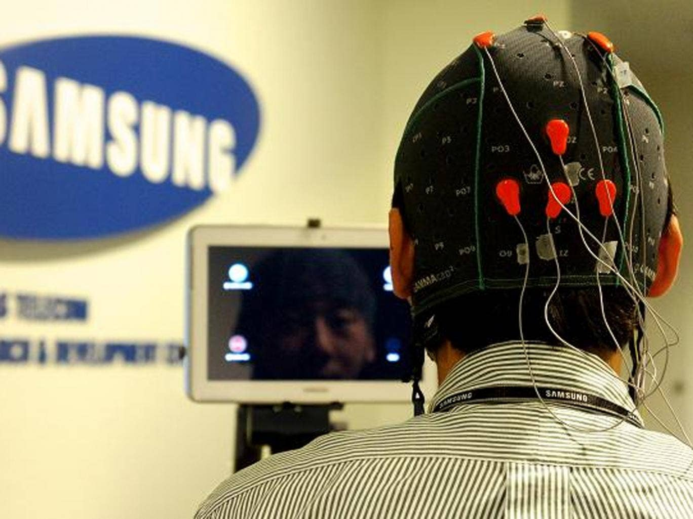 The user wears a cap fitted with EEG electrodes to monitor brain activity