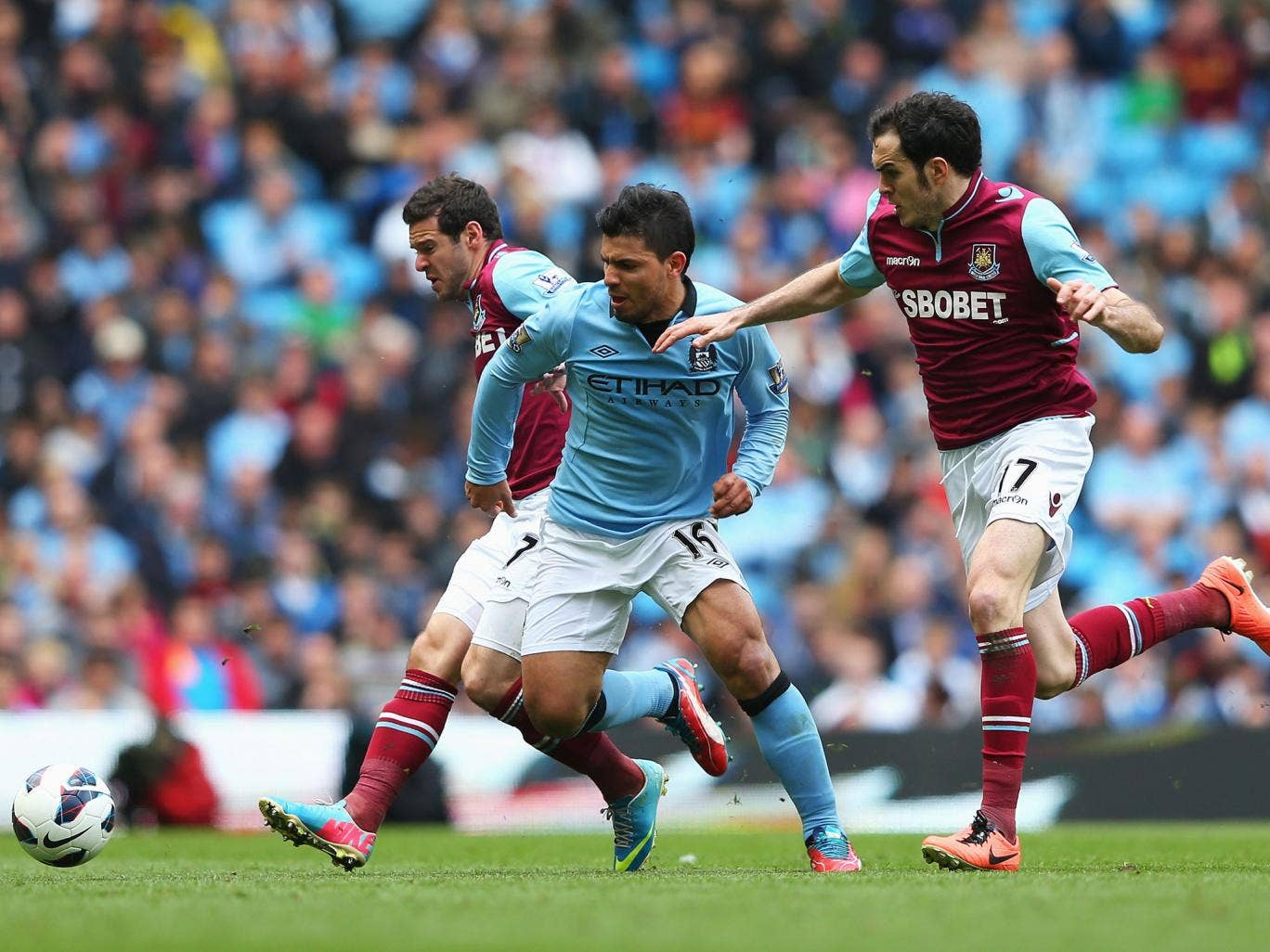 Sergio Aguero of Manchester City is challenged by Matt Jarvis (L) and Joey O'Brien of West Ham United