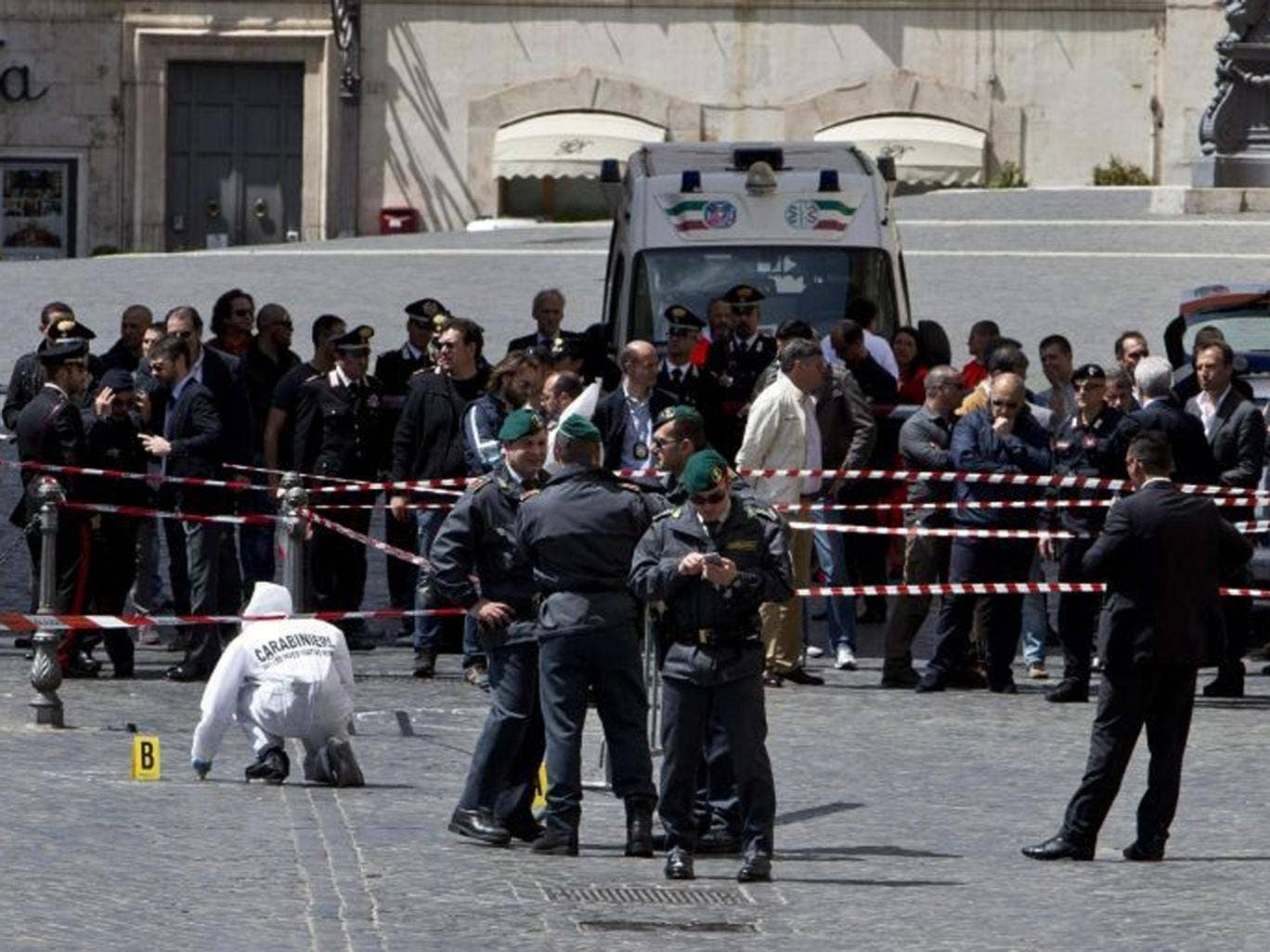 Forensic police investigate the site of a shooting outside Palazzo Chigi, the Italian Prime Minister's offices