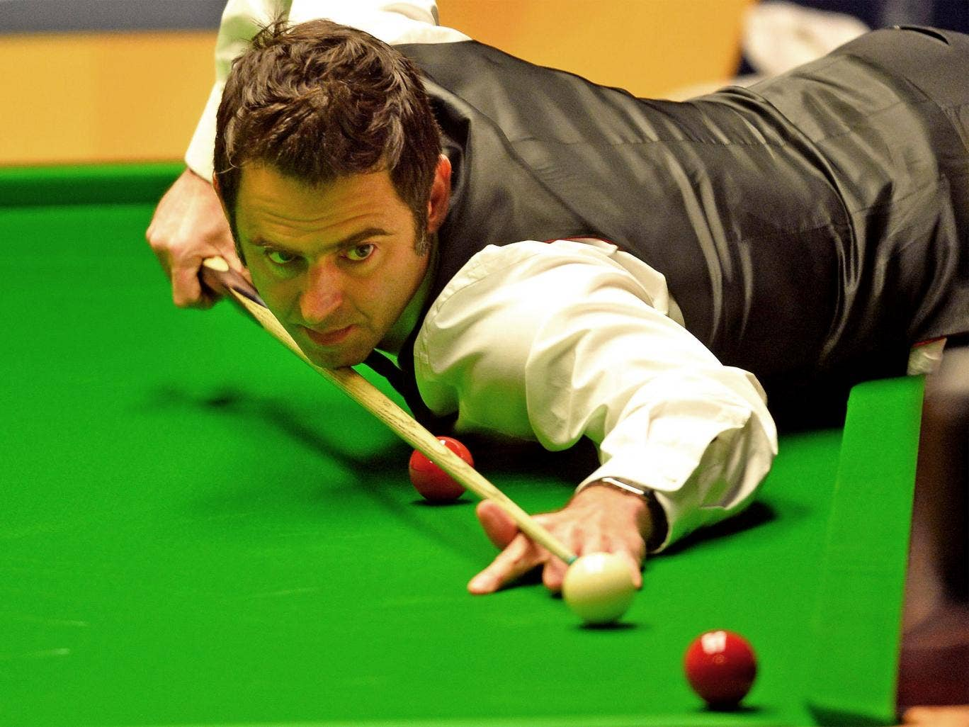 Ronnie O'Sullivan leans over the table to play a shot