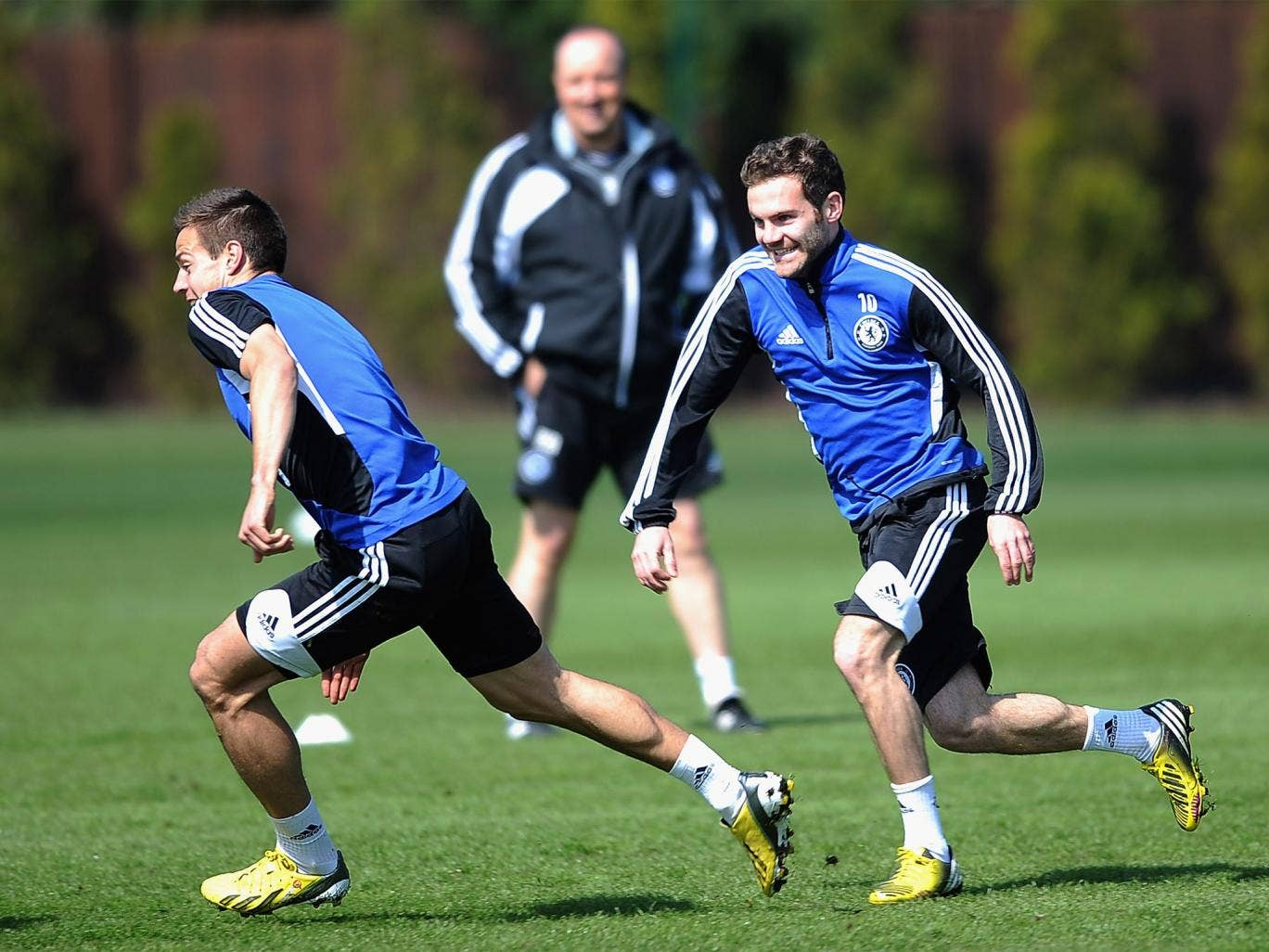 Juan Mata (right) and Cesar Azpilicueta enjoy training yesterday as Rafa Benitez looks on