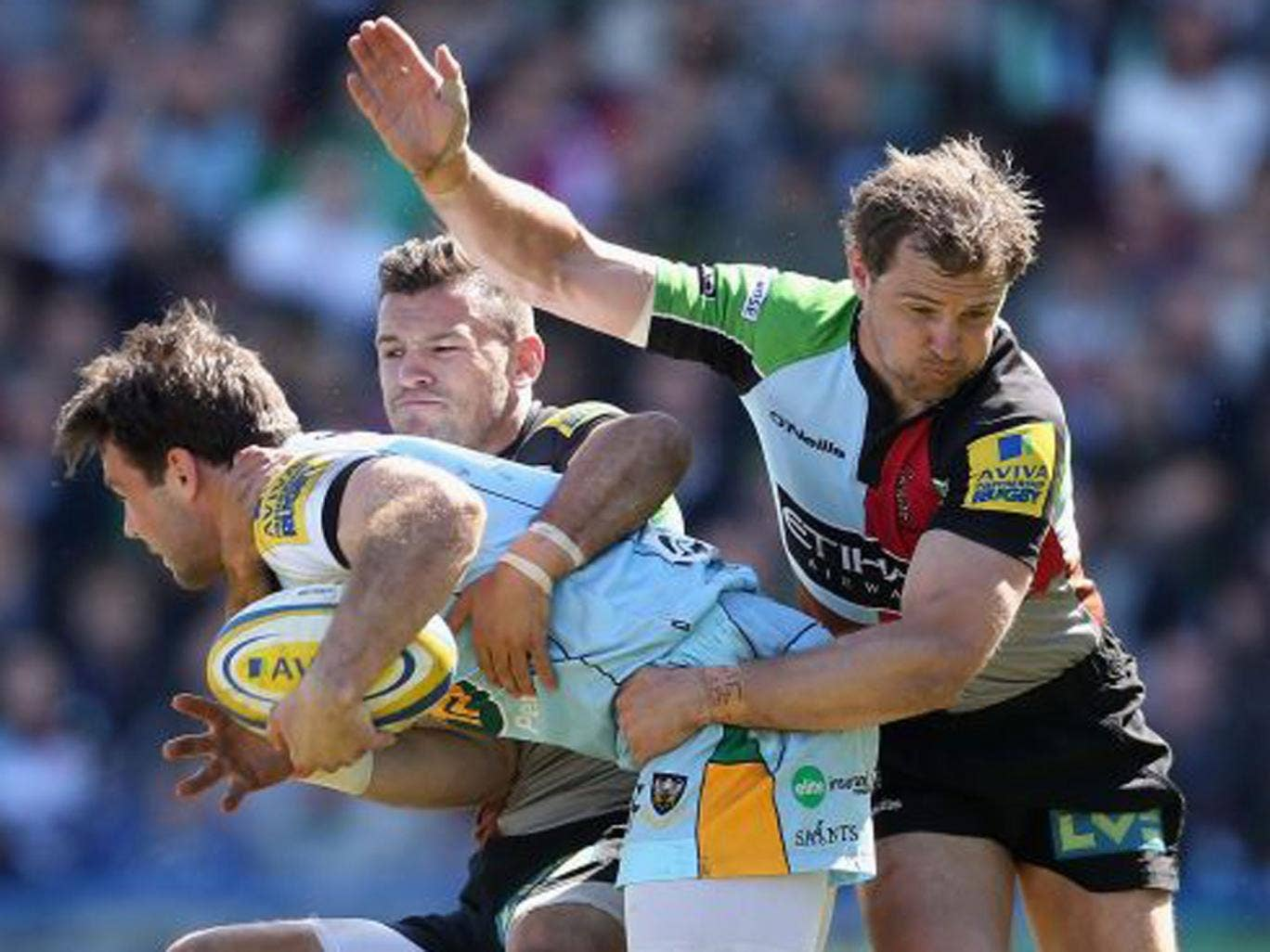 Harlequins' Danny Care and Nick Evans get to grips with Northampton's Ben Foden