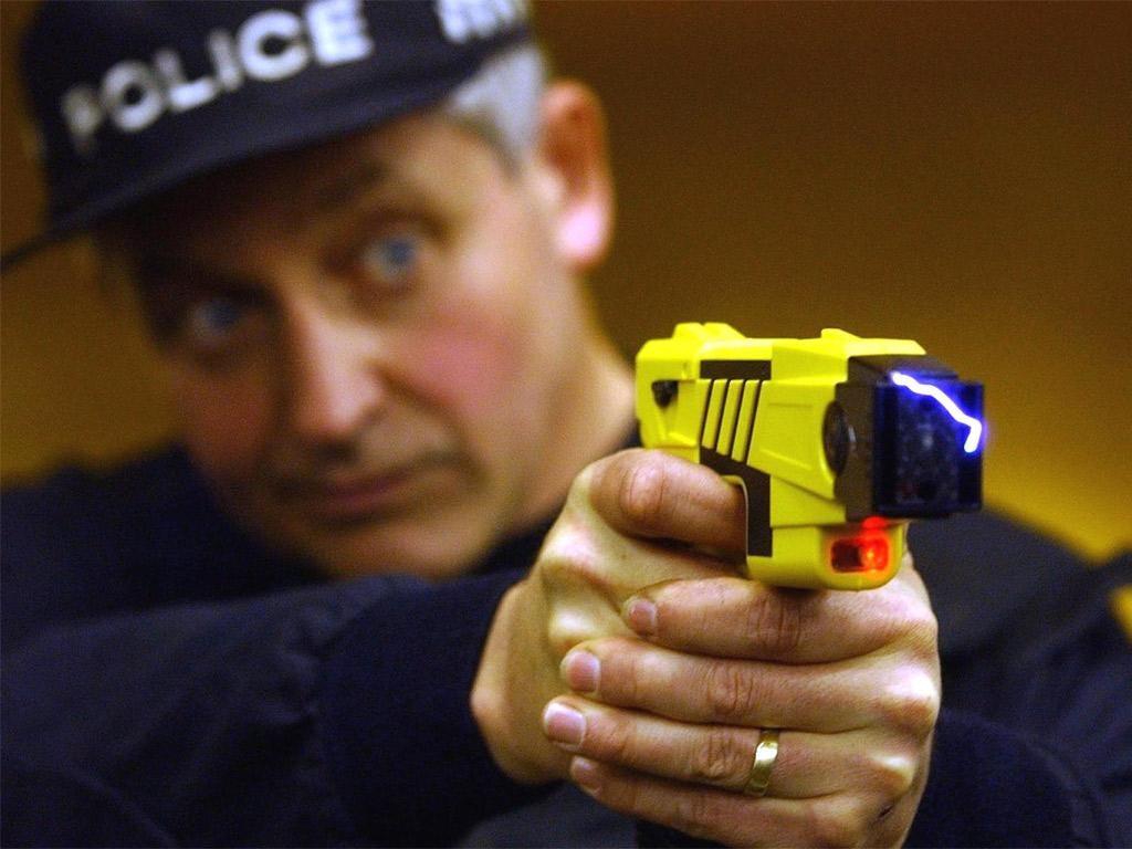 A policeman fires a Taser gun.