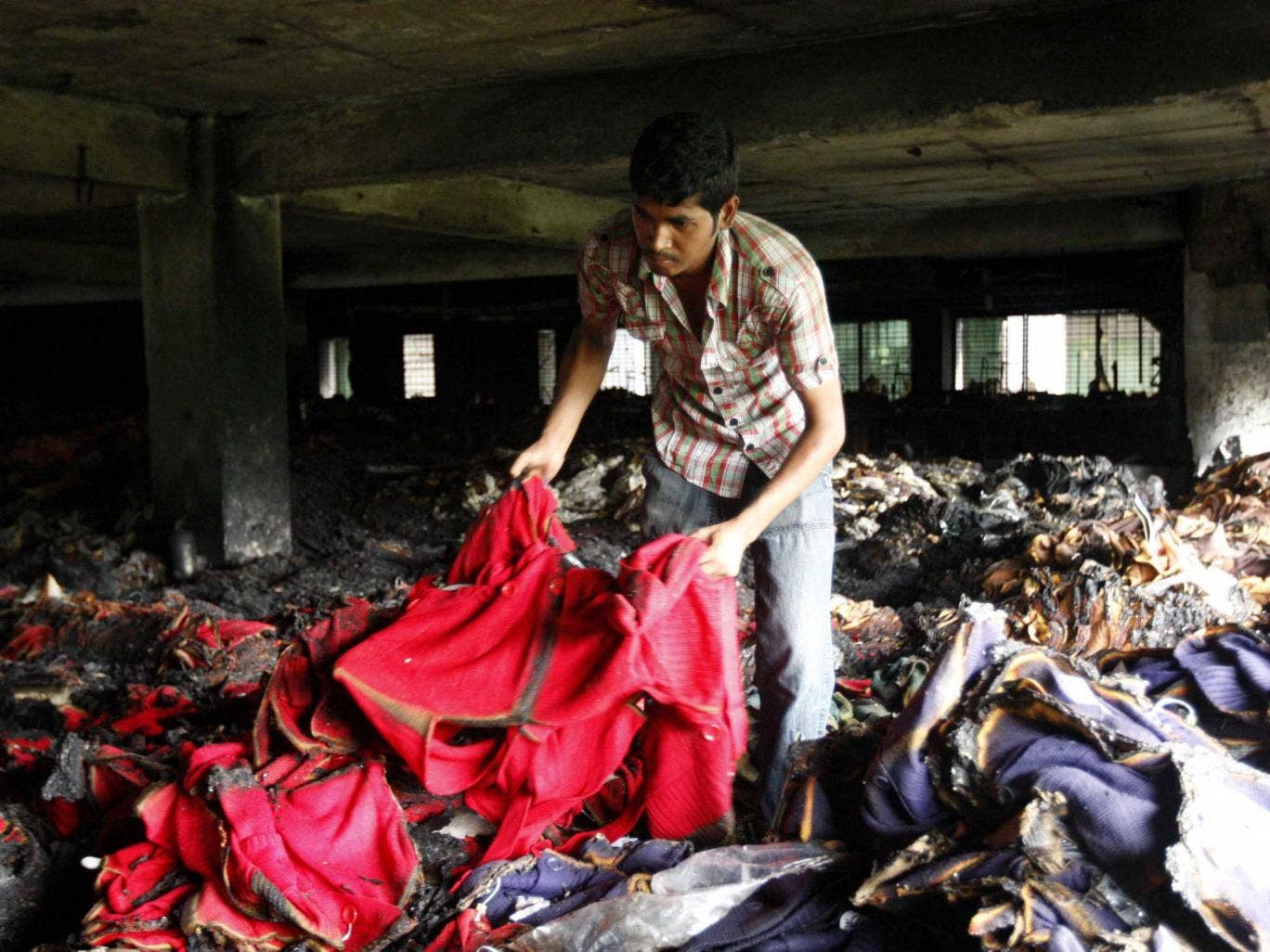 A worker inspects burnt sweaters on the second floor of the building of the readymade garment factory after the devastating fire