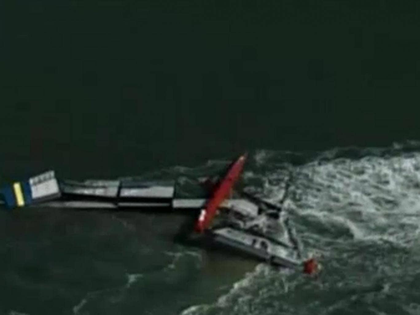 The capsized catamaran is towed back to shore