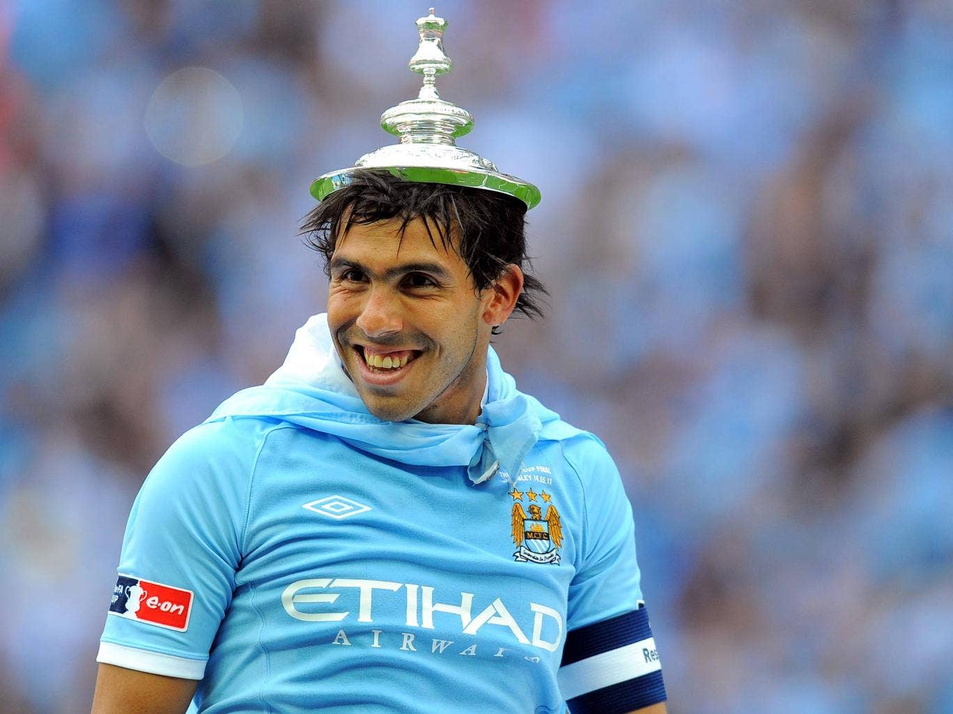 Carlos Tevez with the FA Cup trophy lid upon his head in 2011