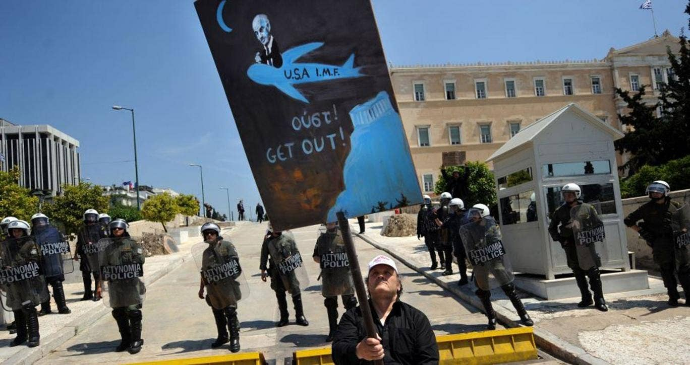 A protester is blocked in by police as he demonstrates against austerity measures in Greece