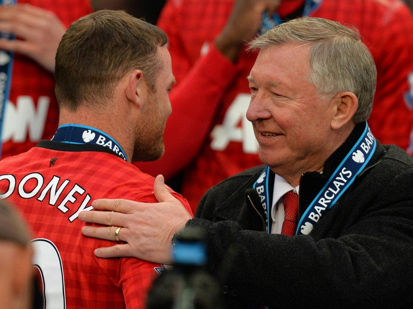 Wayne Rooney receives a pat on the back from Sir Alex Ferguson as Manchester United are awarded the Premier League trophy