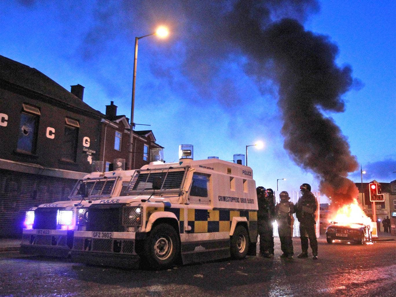 Police stand by their armoured vehicles as a car burns following violence east Belfast in January