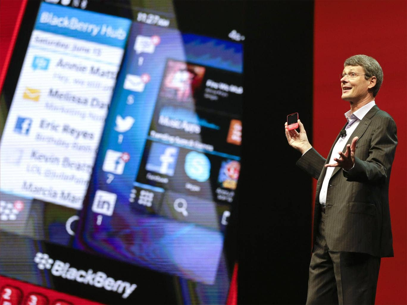 BlackBerry CEO Thorsten Heins holds up the new BlackBerry 10 at a conference in Florida on Tuesday