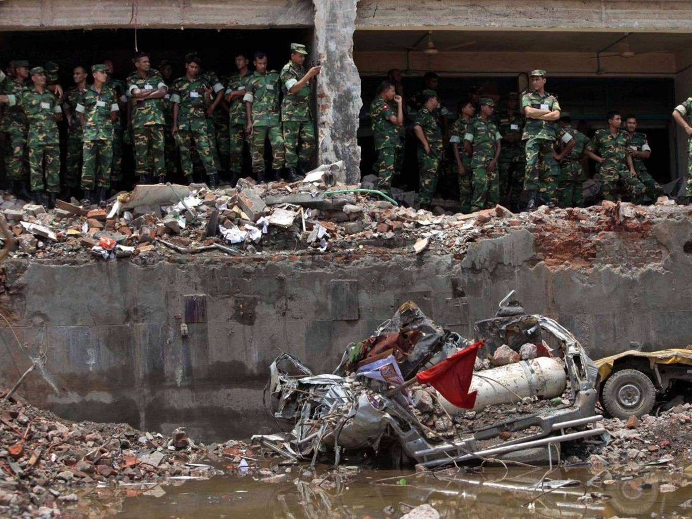 Bangladesh army soldiers stand at the wreckage of a Bangladeshi garment factory building to offer prayers for the souls of the 1,127 people who died in the structure's collapse last month (AP)
