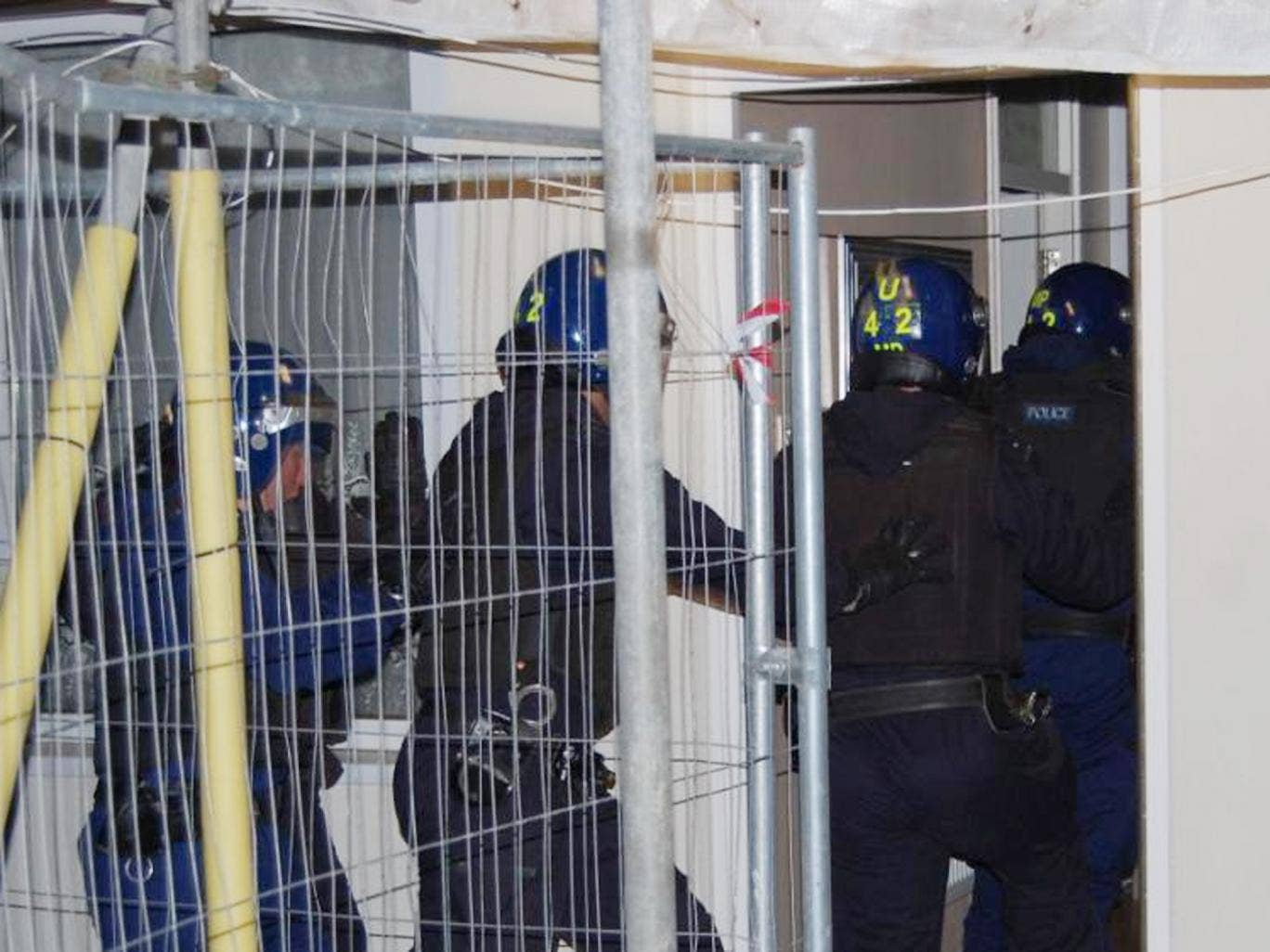 Met officers enter a property during raids as part of Operation Carbon