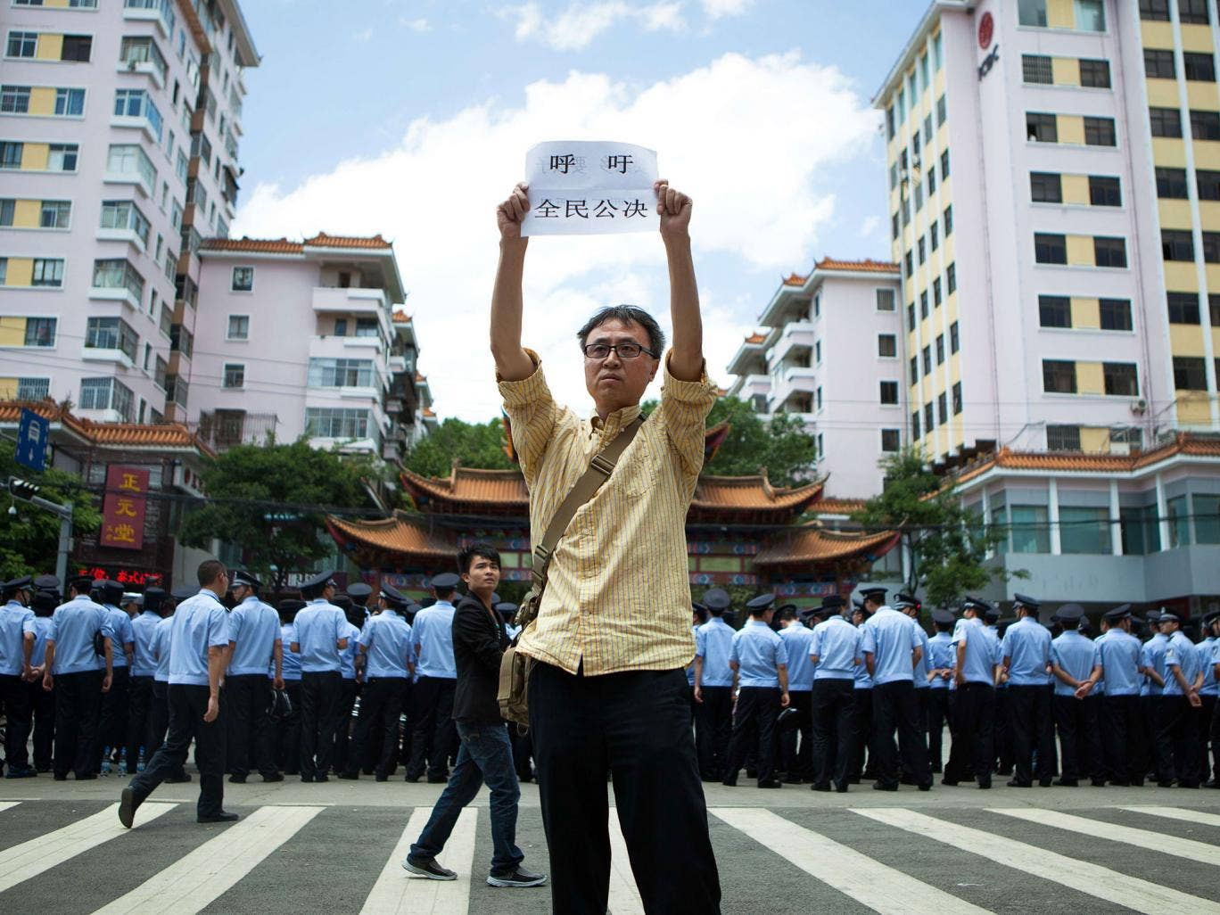 A demonstrator stands firm outside a government building in China's Yunnan province