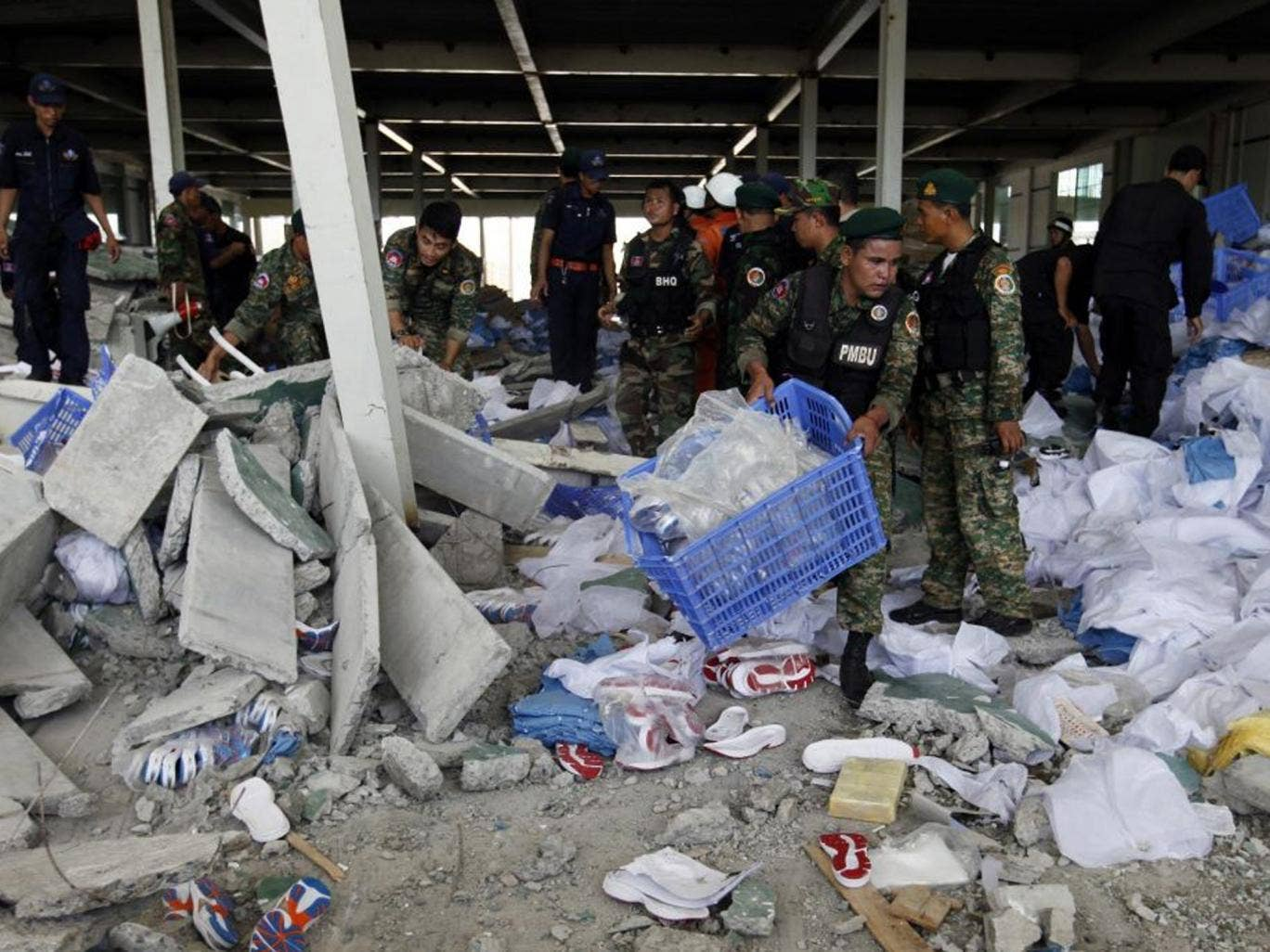 Cambodian officers search the wreckage after the factory collapse