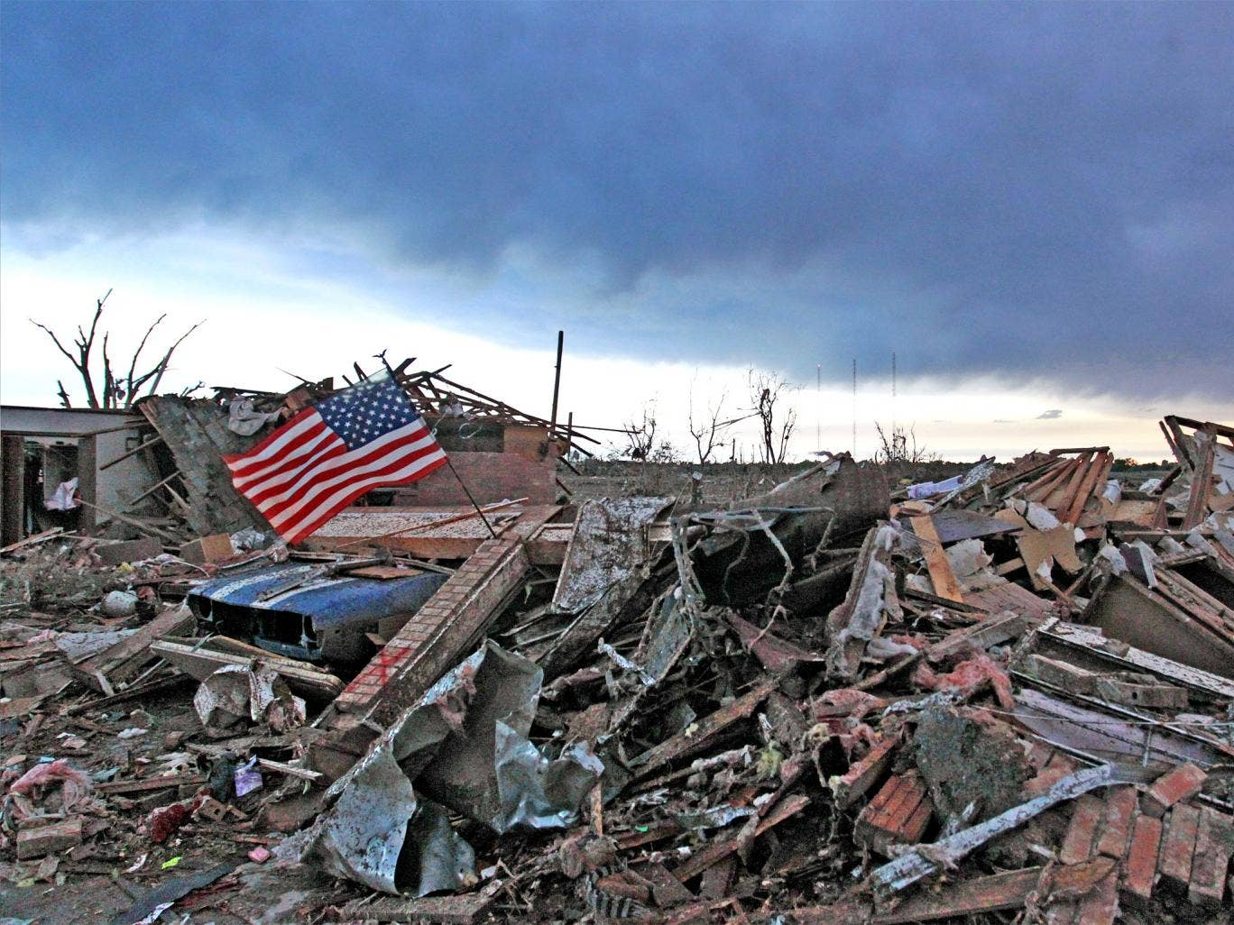 An American flag blows in the wind at sunrise atop the rubble of a destroyed home