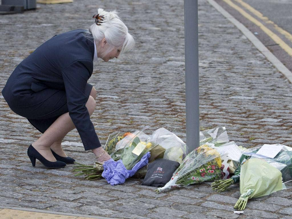 A woman places flowers outside the Royal Military Barracks, near the scene where a man was killed in Woolwich