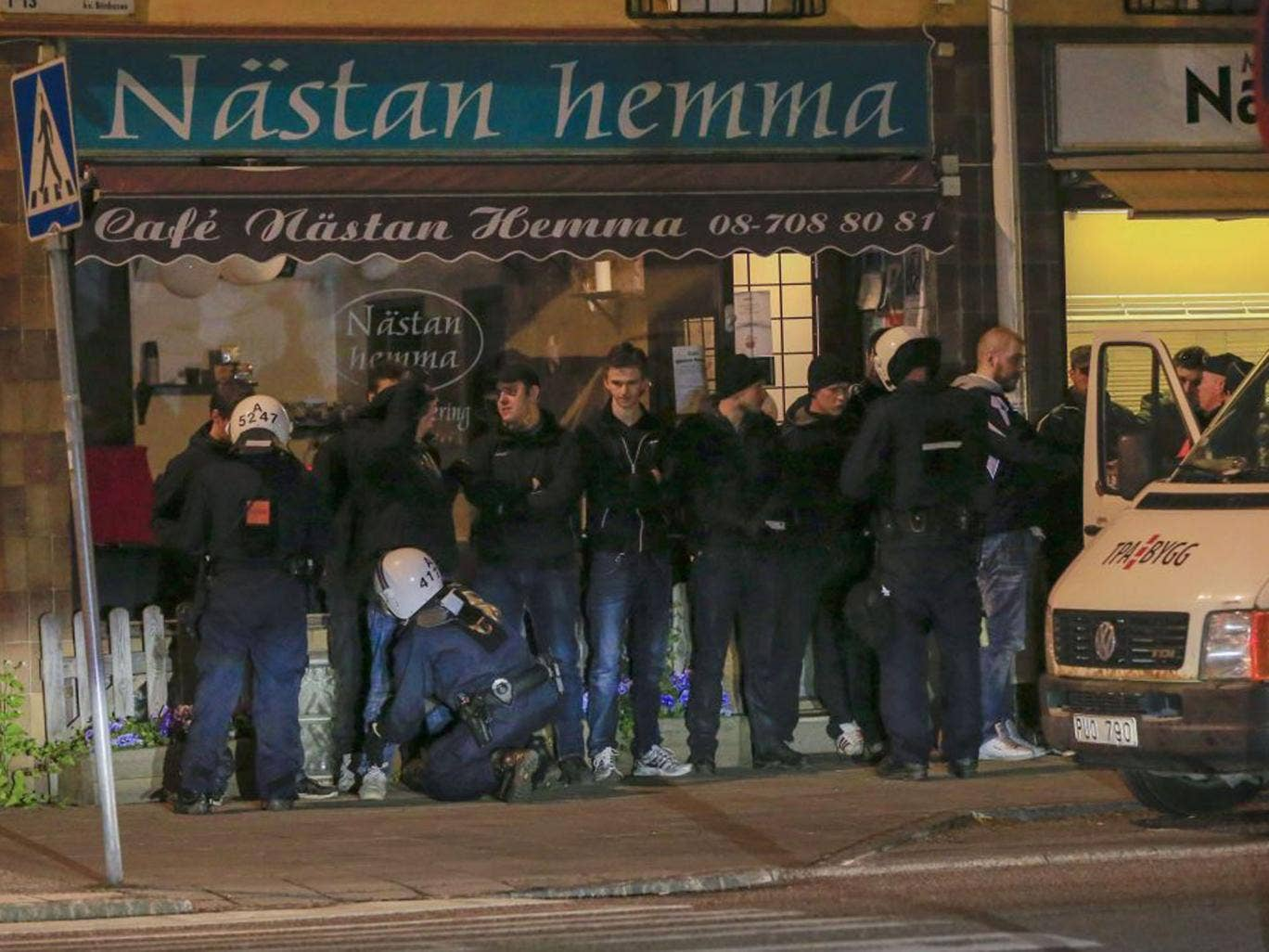 Police officers search young men lined up against a wall in a suburb of Stockholm (Fredrik Persson/AFP/Getty Images)