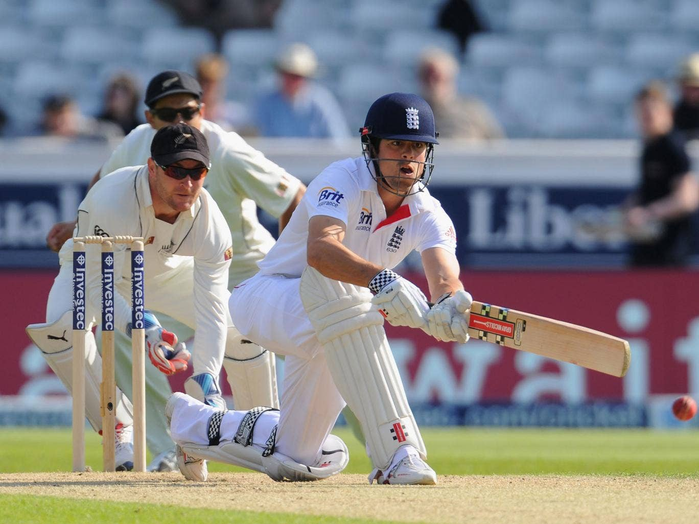 Alastair Cook prepares to sweep watched by wicketkeeper Brendon McCullum