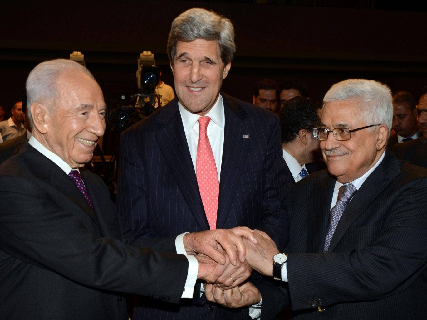 Mahmoud Abbas and Peres who posed for a three-way handshake with US Secretary of State John Kerry