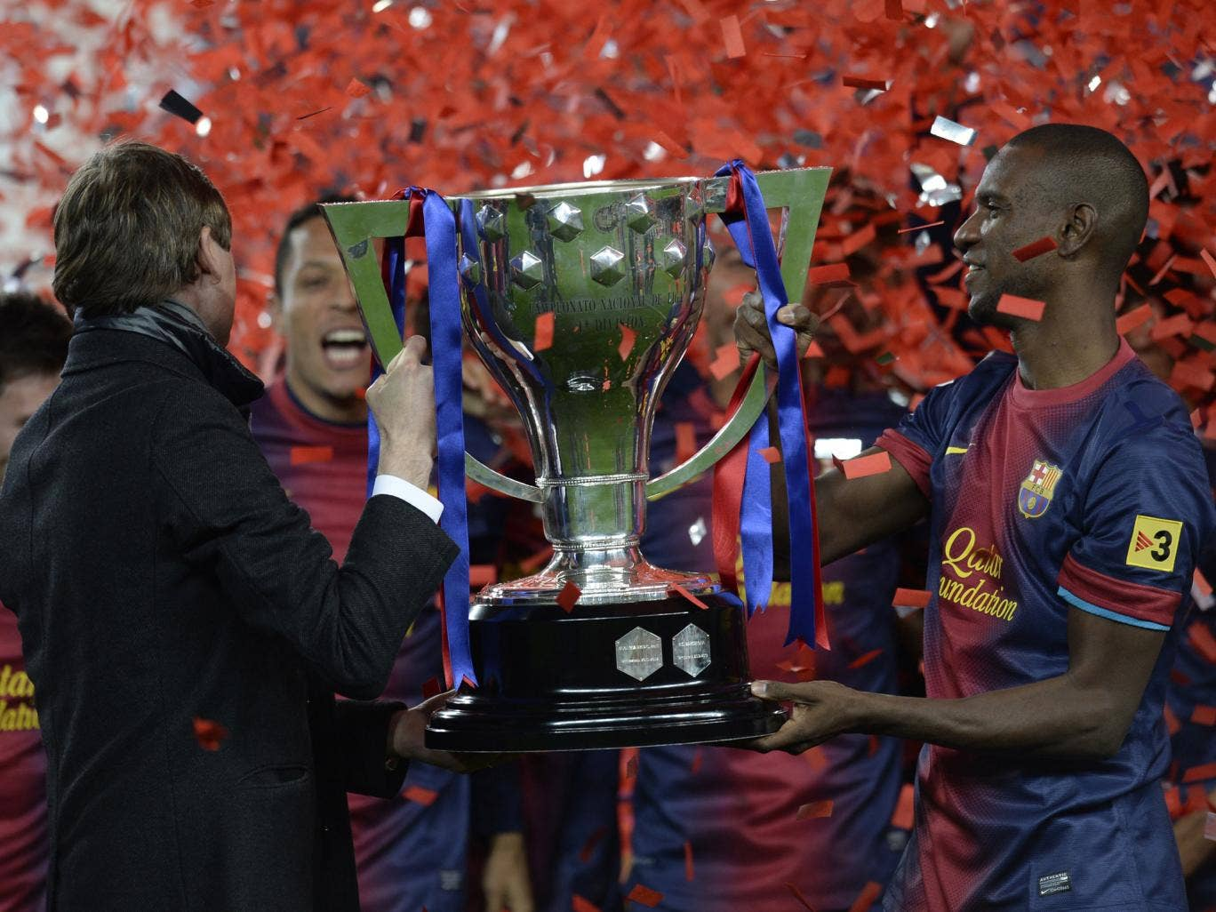 Tito Vilanova (L) and Eric Abidal life the league trophy during a ceremony at the Camp Nou