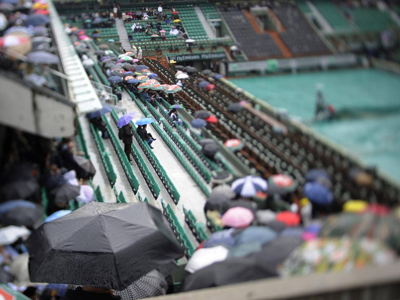 People wait on the Philippe Chatrier central court as rain stops play on day five of the French