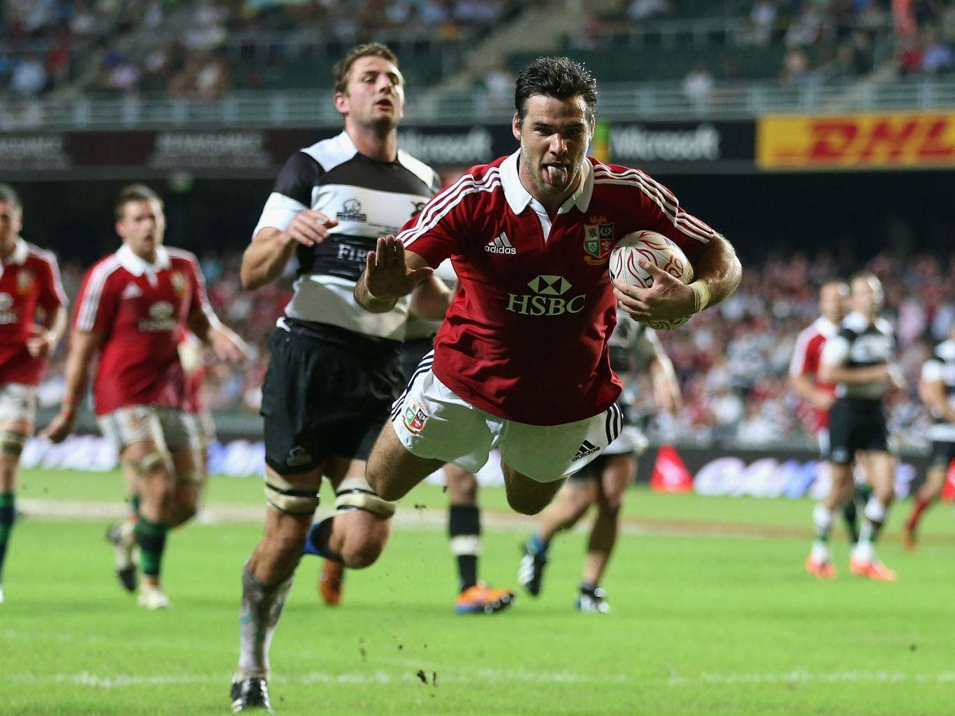 Tongue lashing: Mike Phillips scores a mouthwatering second try as the Lions open their summer tour with a 59-8 thrashing of the Barbarians in Hong Kong yesterday
