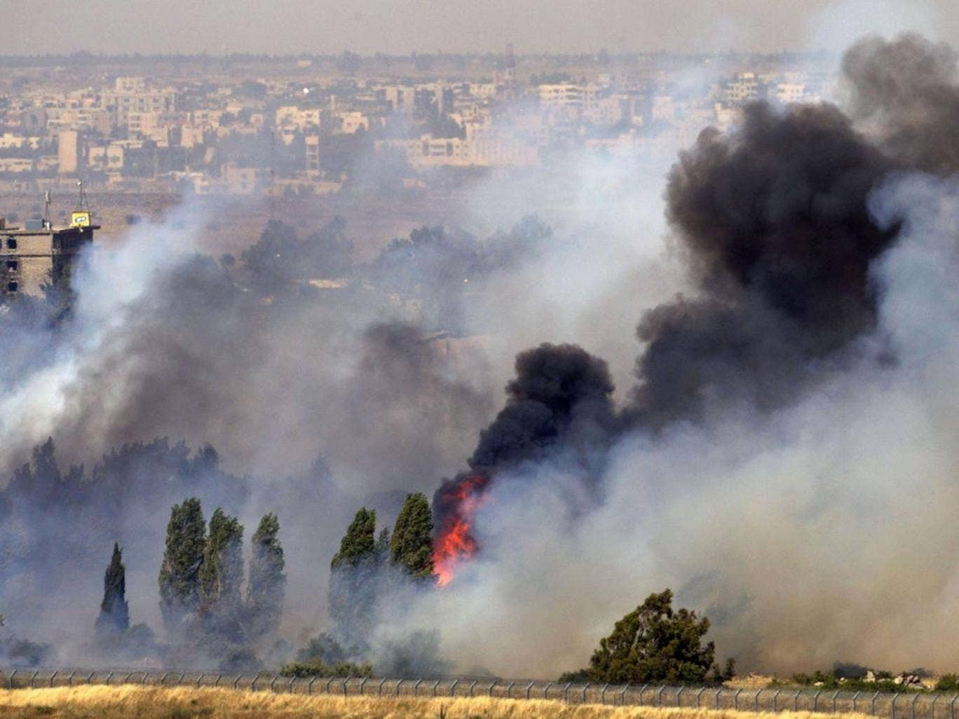 A picture taken on June 6, 2013 from the Israeli side along the Israel-Syria ceasefire line in the Golan Heights shows smoke billowing from a fire caused by clashes between Syrian rebels and forces loyal to the regime near the Quneitra crossing