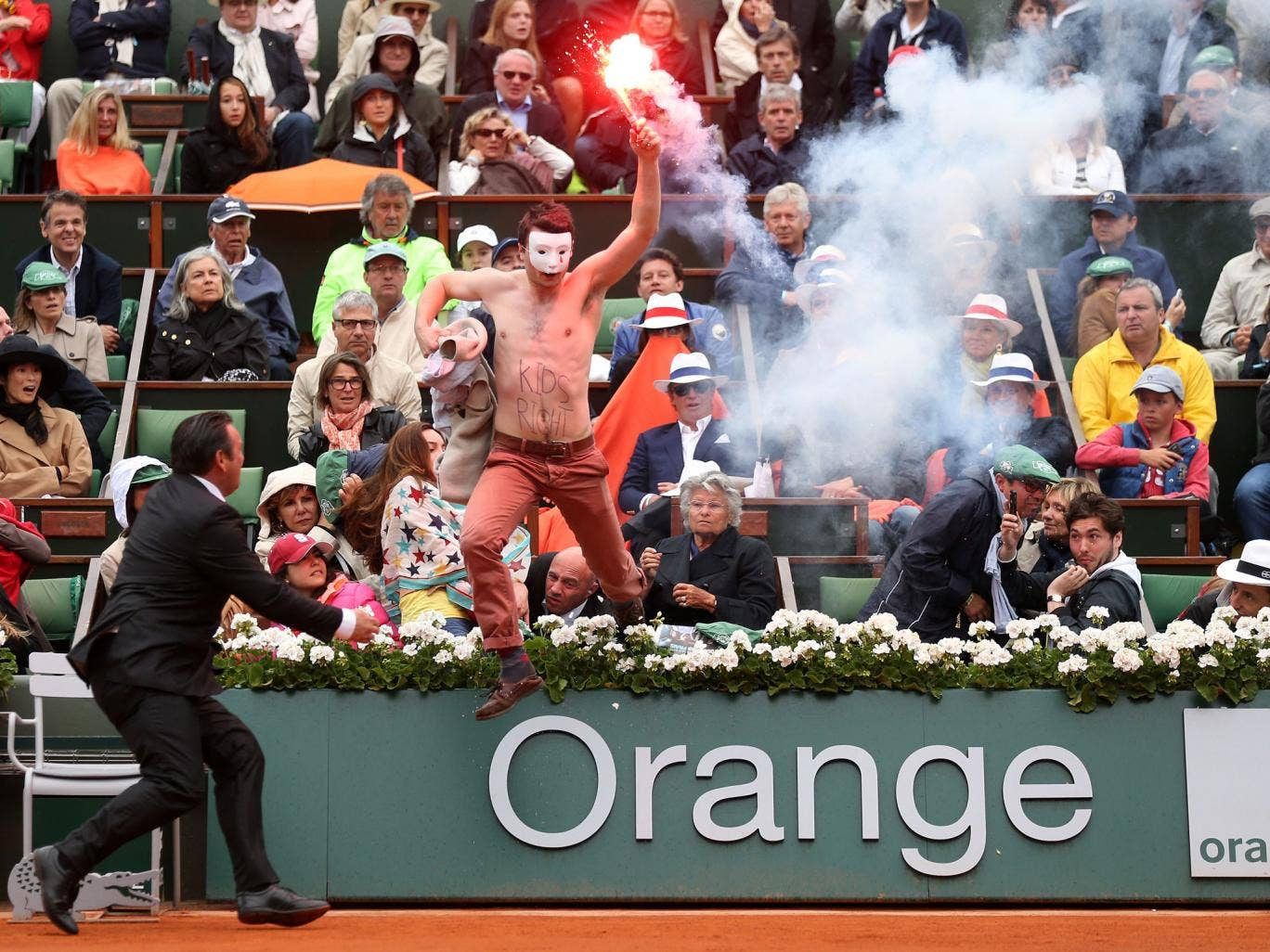 A protester runs onto court with a lit flare before the start of a game in the Men's Singles final
