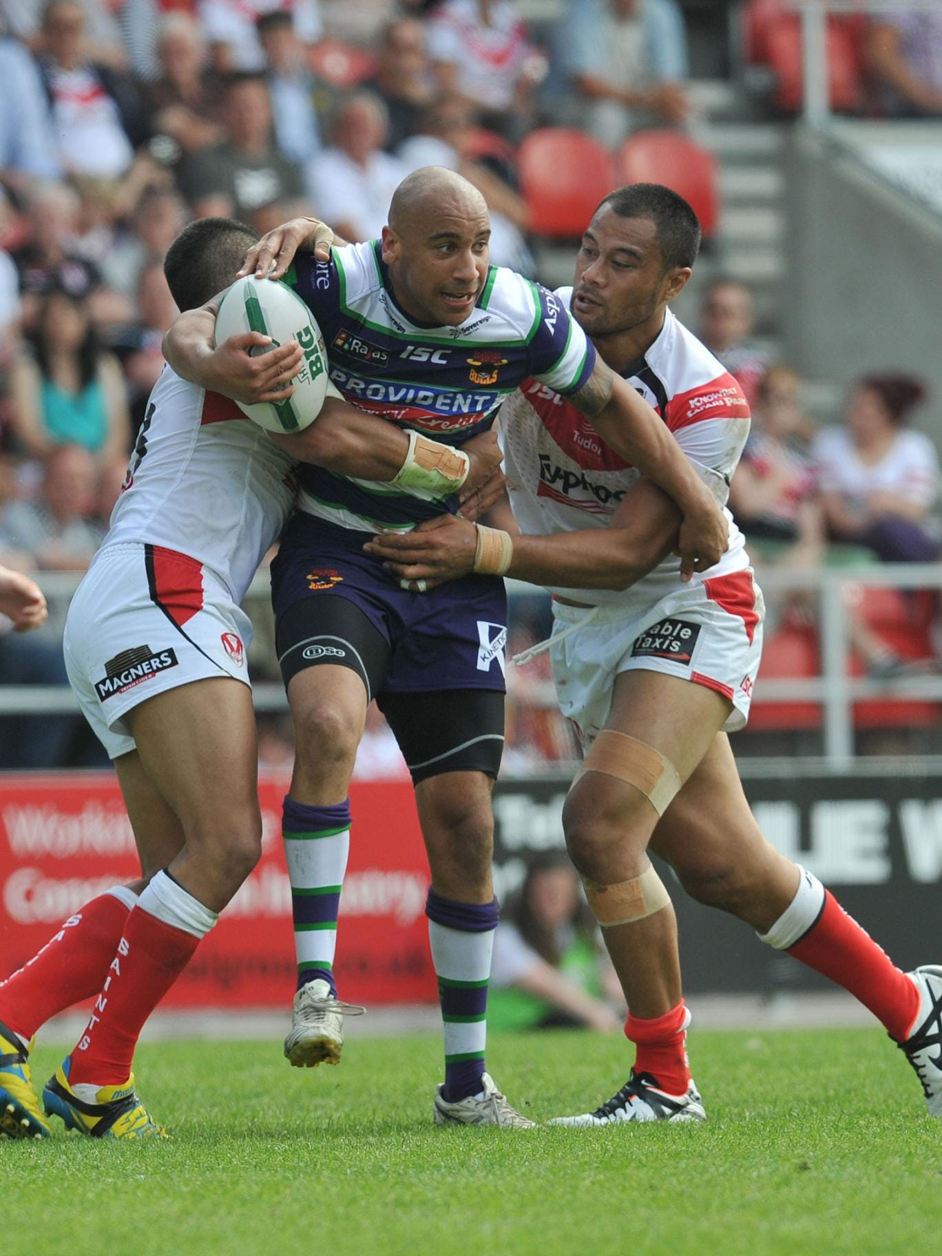 Bradford's Matty Blythe, centre, is tackled by St Helens' Willie Manu, left, and Tony Puletua, right, as the home team prove to be too strong for the Bulls