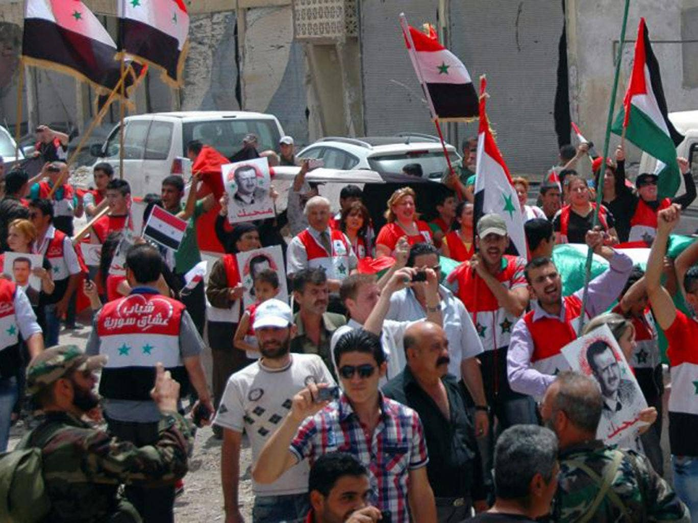 People jubilating in the center of Qusayr as they celebrate the Syrian government's recapture of the town earlier in the week after nearly three weeks of heavy fighting