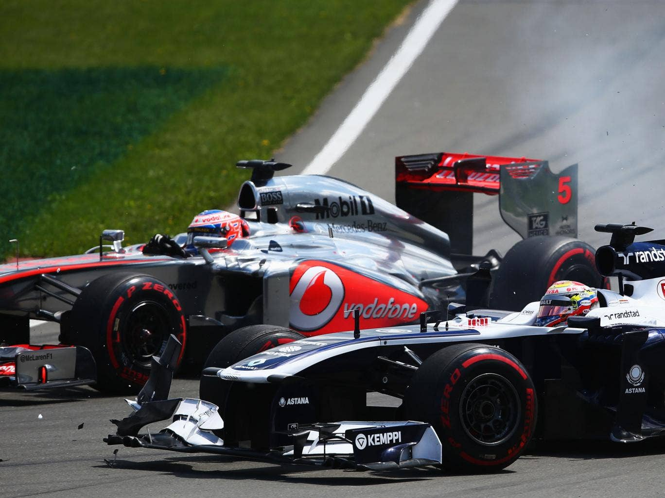 Jenson Button of Great Britain and McLaren and Pastor Maldonado of Venezuela and Williams drive side by side into the hairpin during the Canadian Formula One Grand Prix