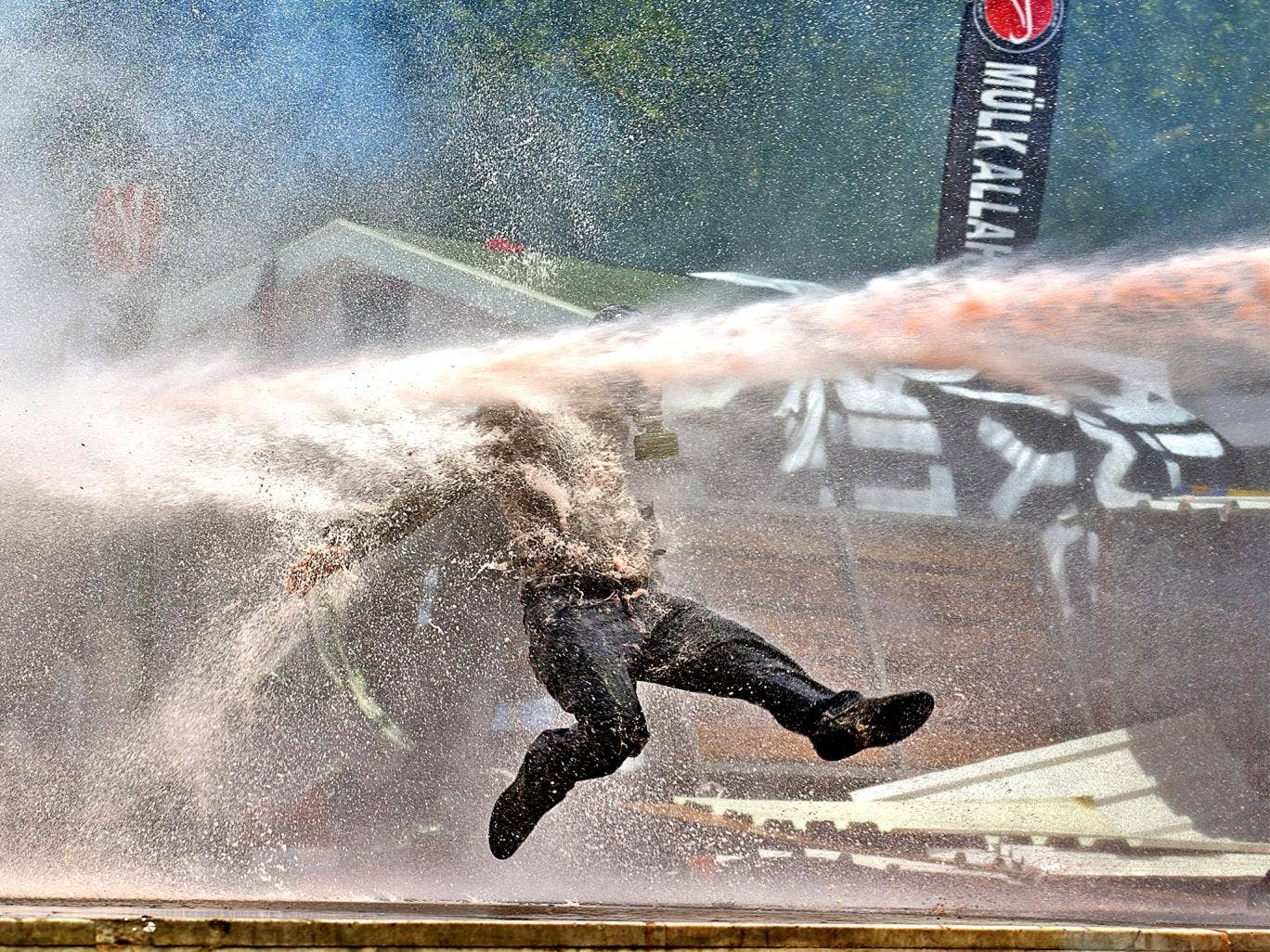 A protestor is hit by water sprayed from a water cannon during clashes in Taksim Square