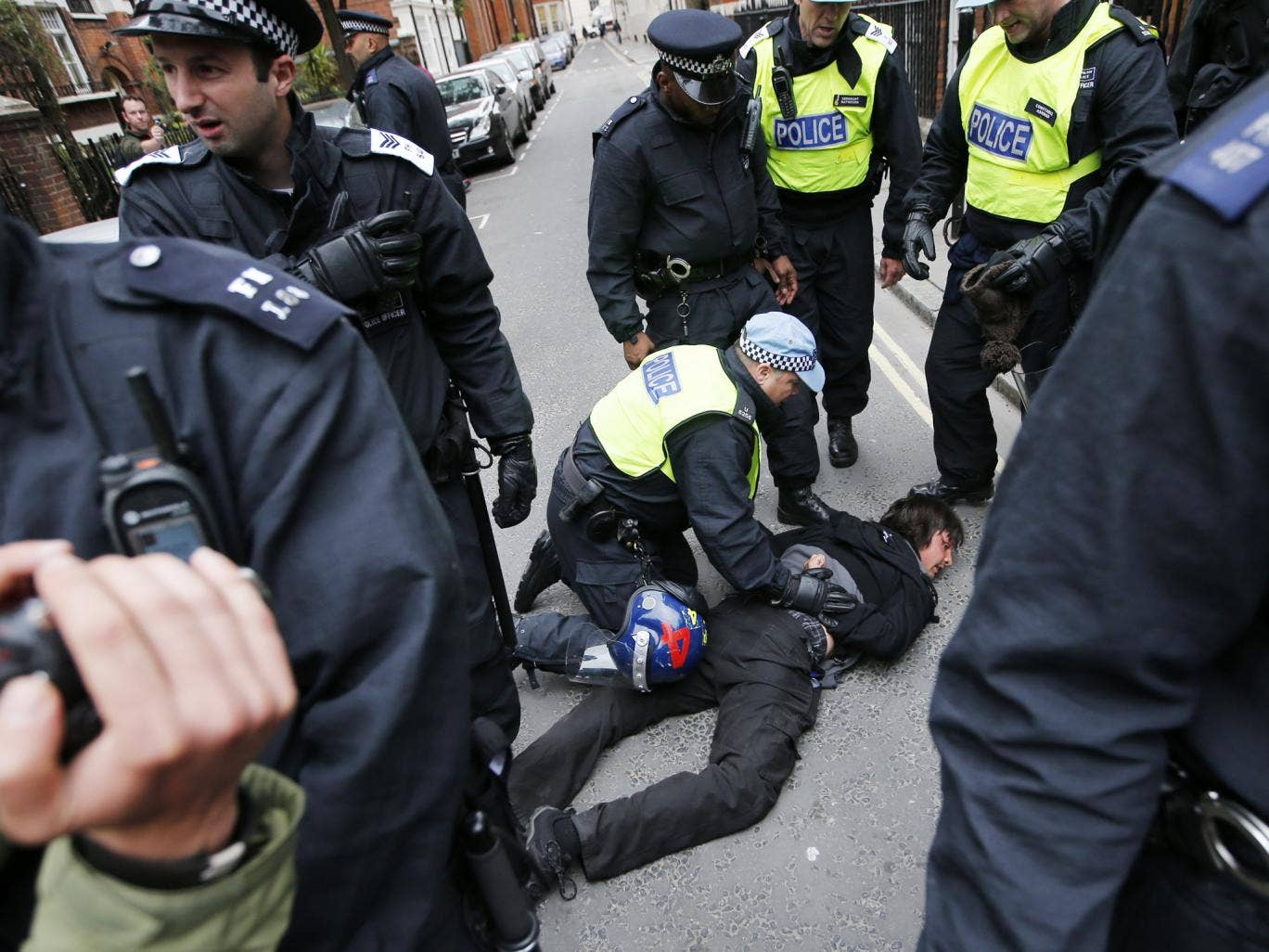 Police detain an anti-capitalist protester in London on 11 June 2013