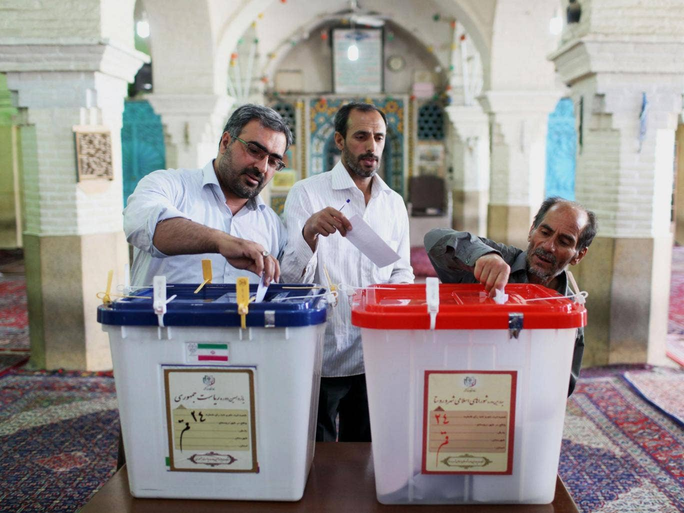 Iranian men cast their ballots during presidential elections at a polling station in Qom, 125 kilometers (78 miles) south of the capital Tehran, Iran