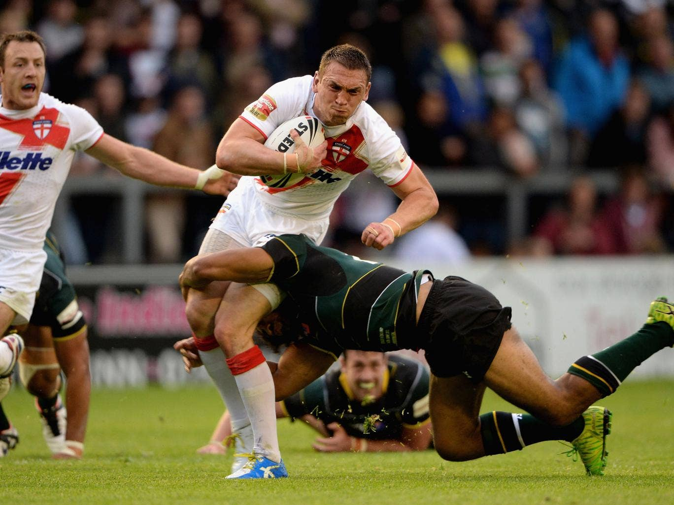 England captain Kevin Sinfield attempts to break the tackle of Sia Soliola